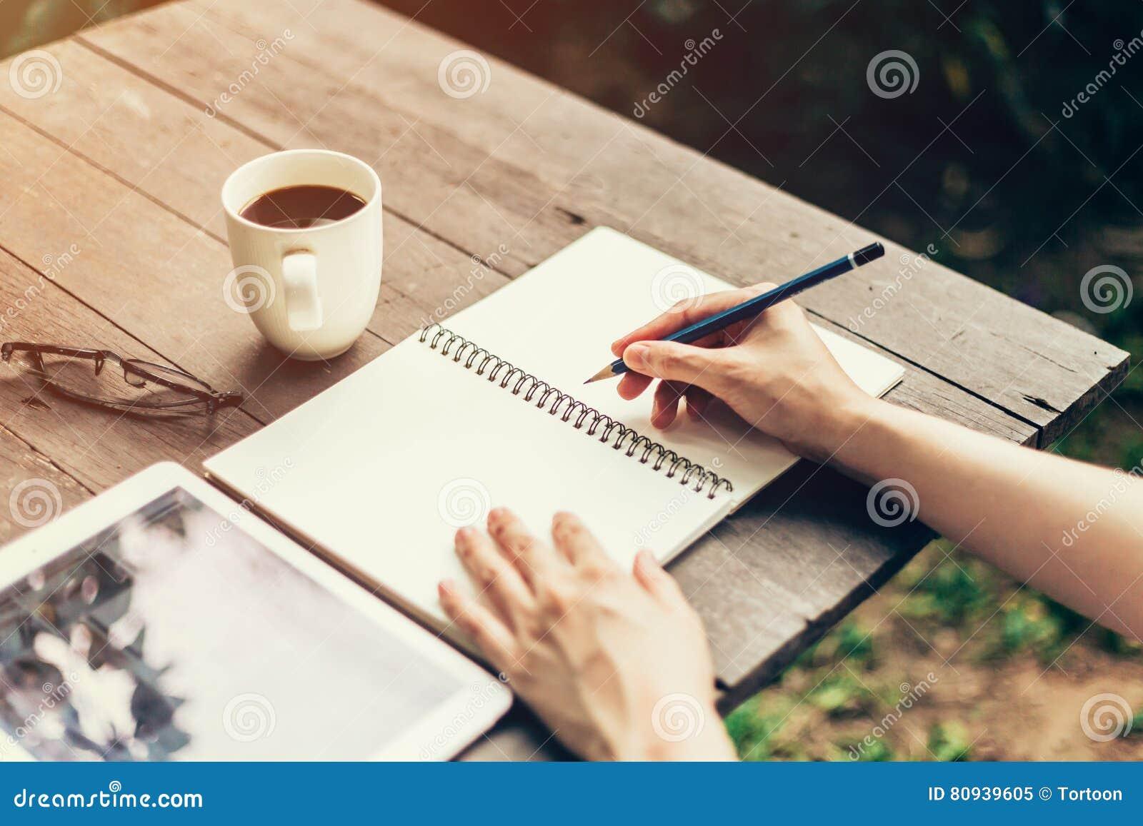 Vrouwelijke hand met potlood die op notitieboekje schrijven Vrouwenhand met pen