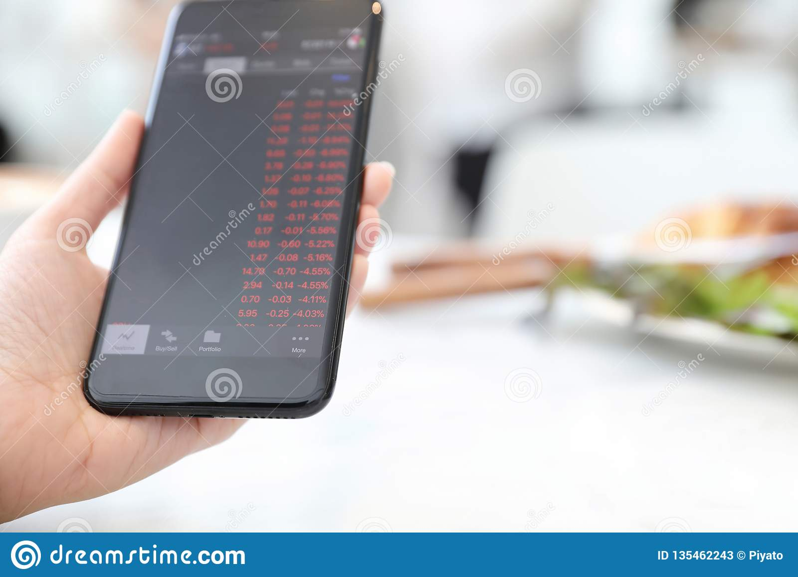 Vrouwelijke hand met smartphone handelvoorraad online in koffiewinkel, Bedrijfsconcept