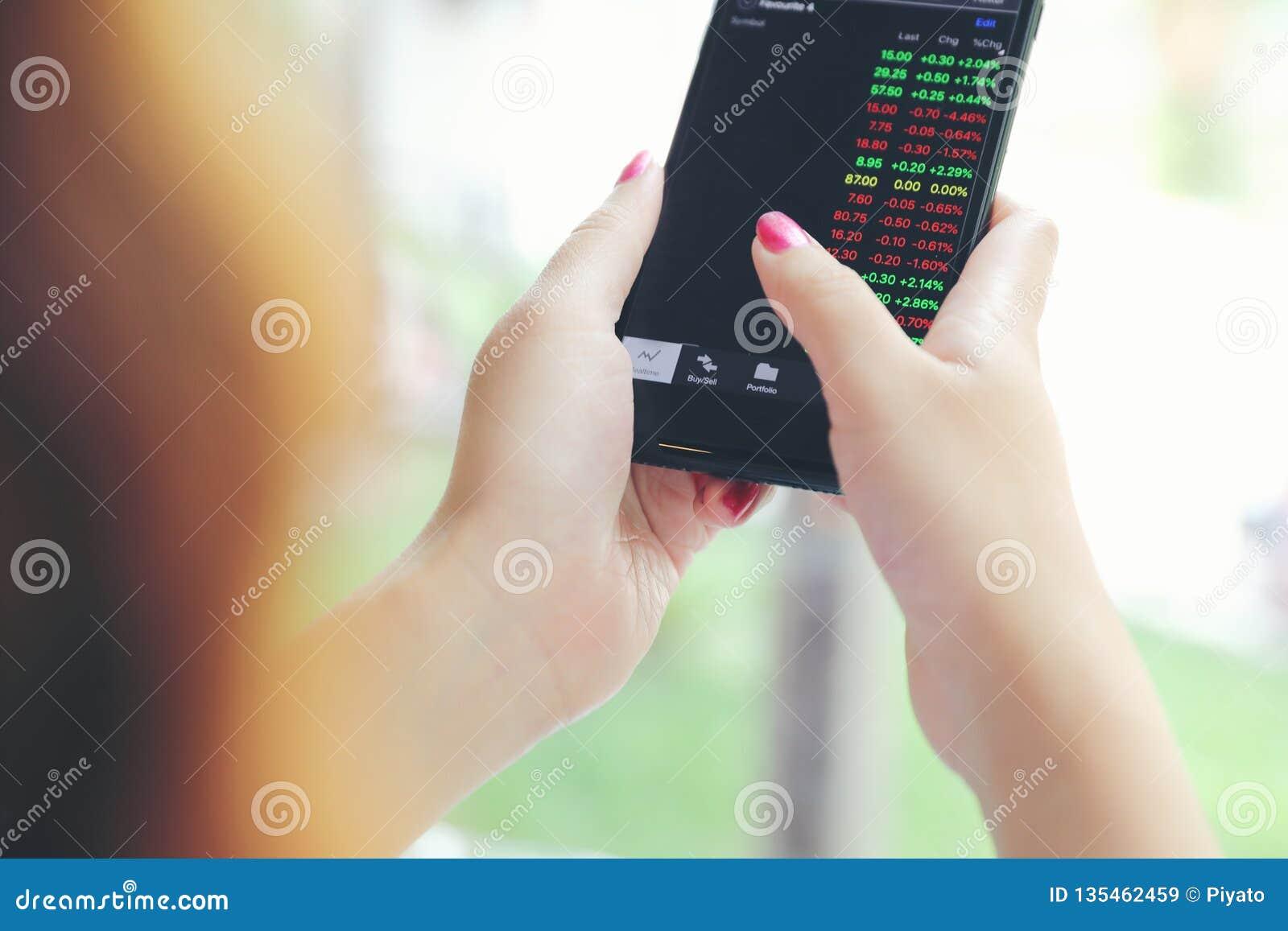 Vrouwelijke hand met smartphone handelvoorraad online, Zaken concep