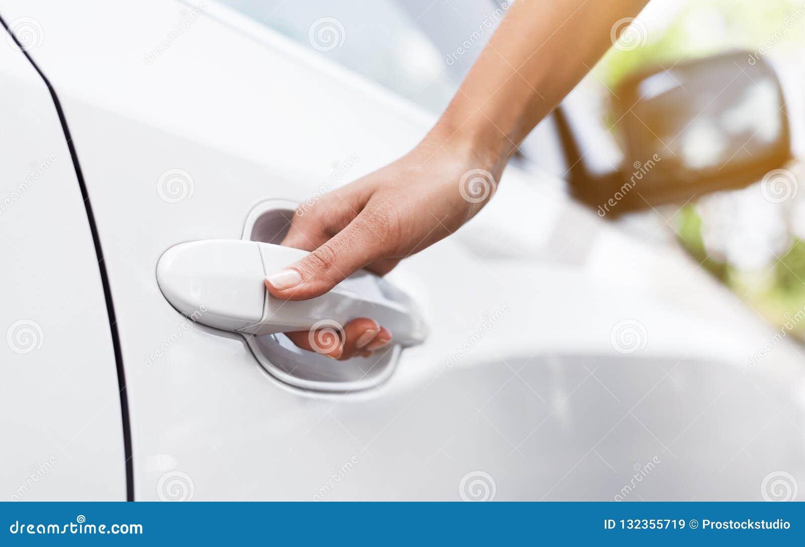 Vrouwelijke hand op het handvat van de autodeur