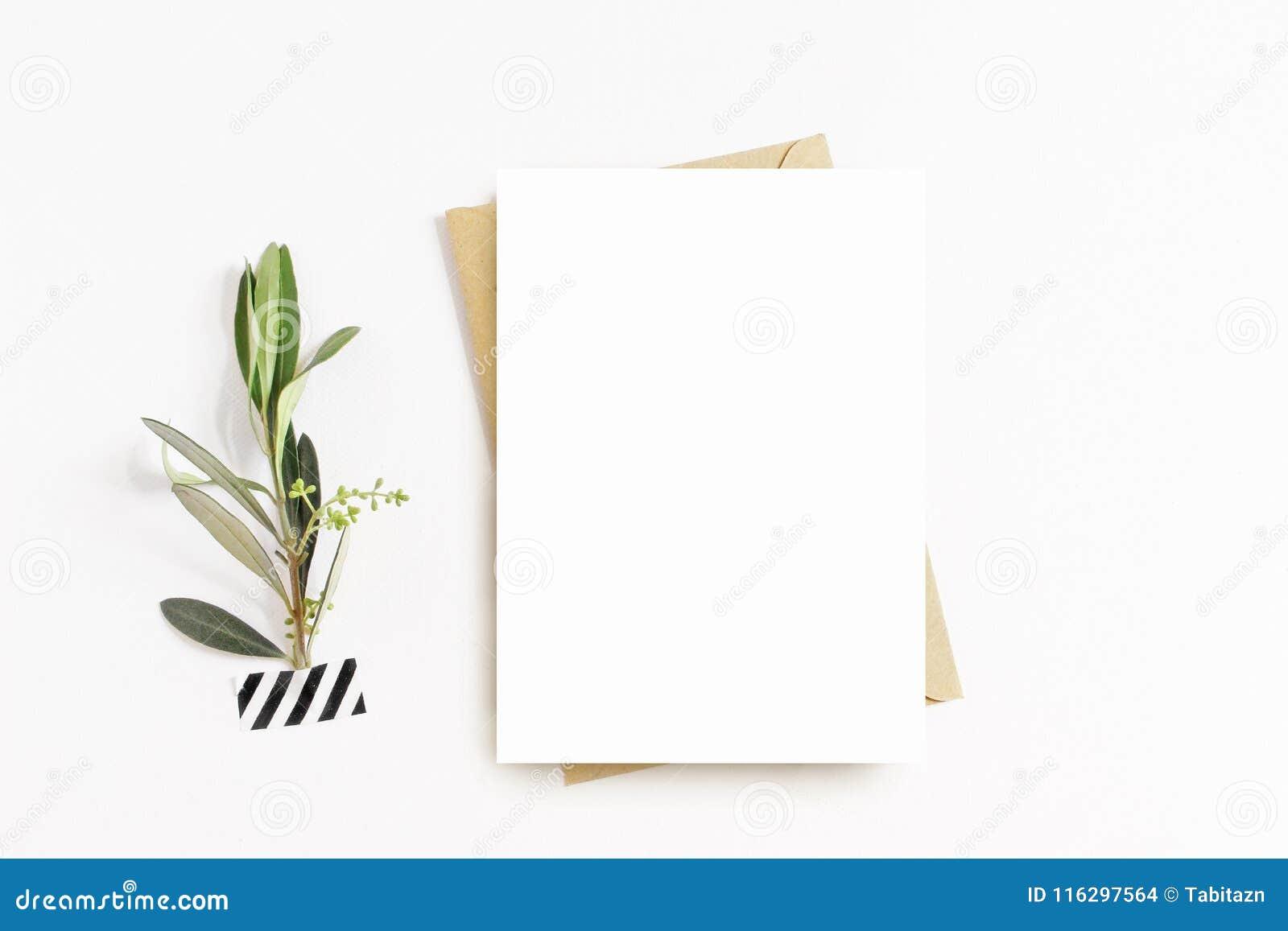 Vrouwelijke kantoorbehoeften, de scène van het Desktopmodel Lege groetkaart, ambachtenvelop, washiband en met olijftak wit