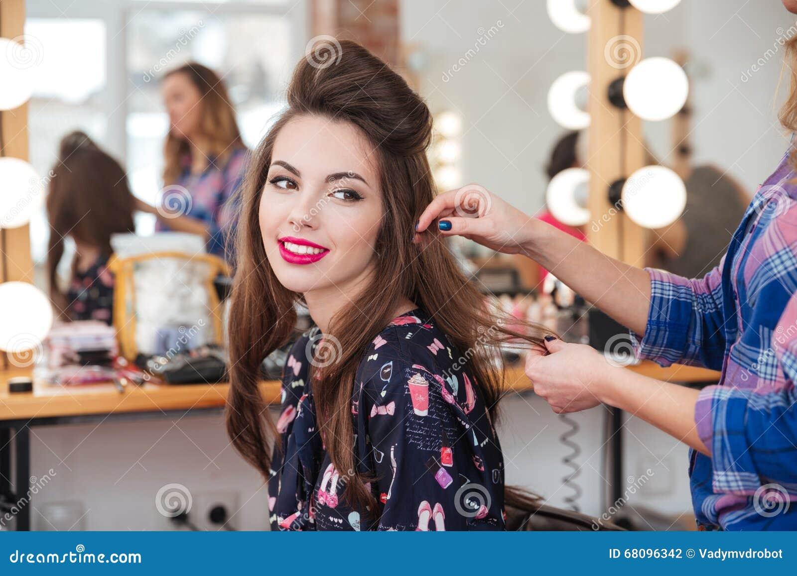 Vrouwelijke kapper die tot kapsel maken aan leuke vrouw in schoonheidssalon