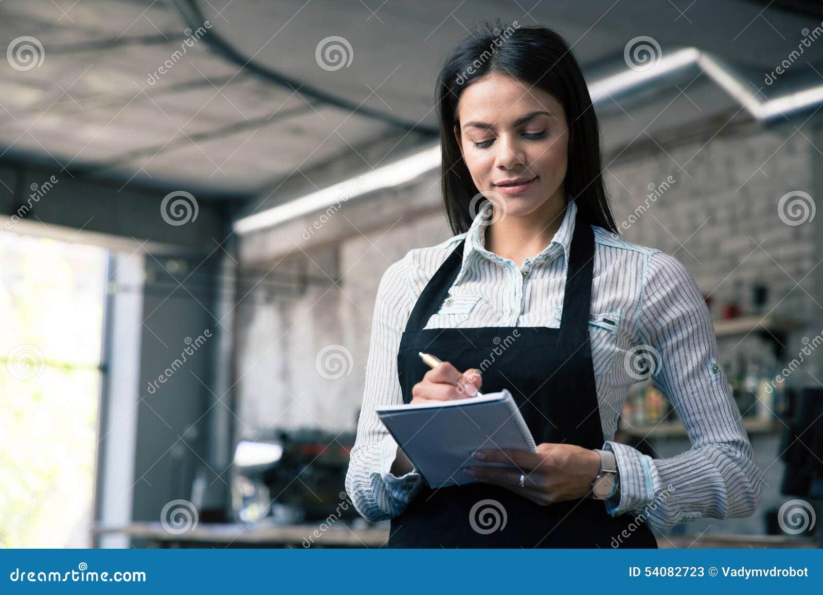 Vrouwelijke kelner in schort het schrijven orde