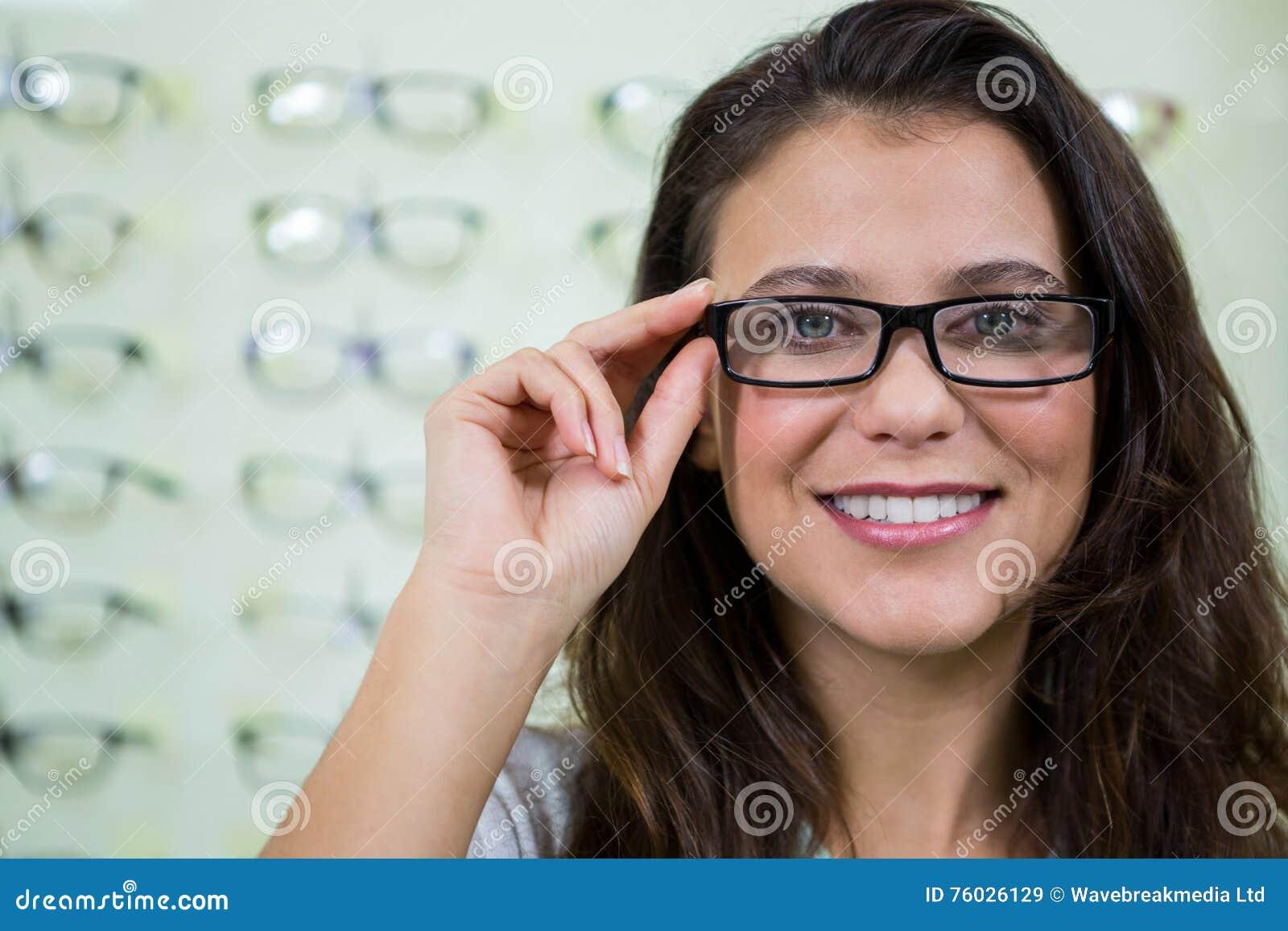 e4248f0137697a Portret van glimlachende vrouwelijke klant die bril in optische opslag  dragen