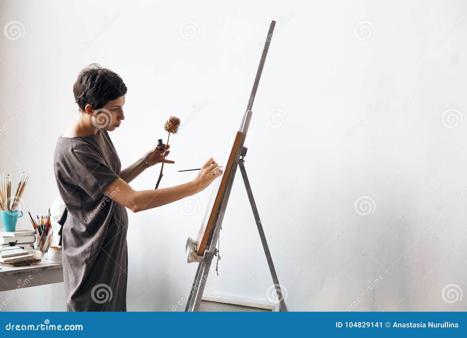 Vrouwelijke kunstenaar in haar ruime witte studio die met waterverf het schilderen werken
