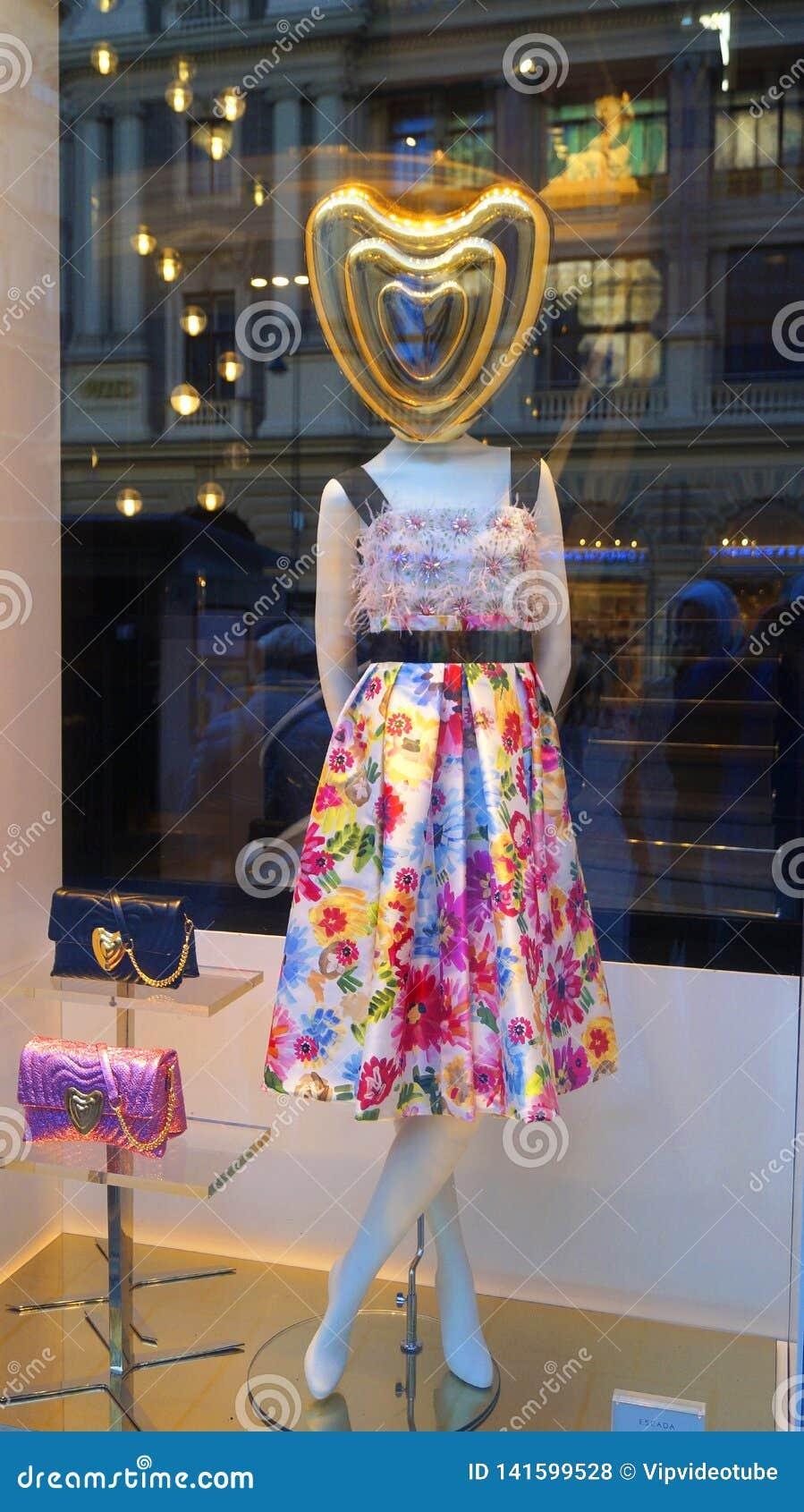 Vrouwelijke ledenpop in modieuze kleding in het winkelvenster