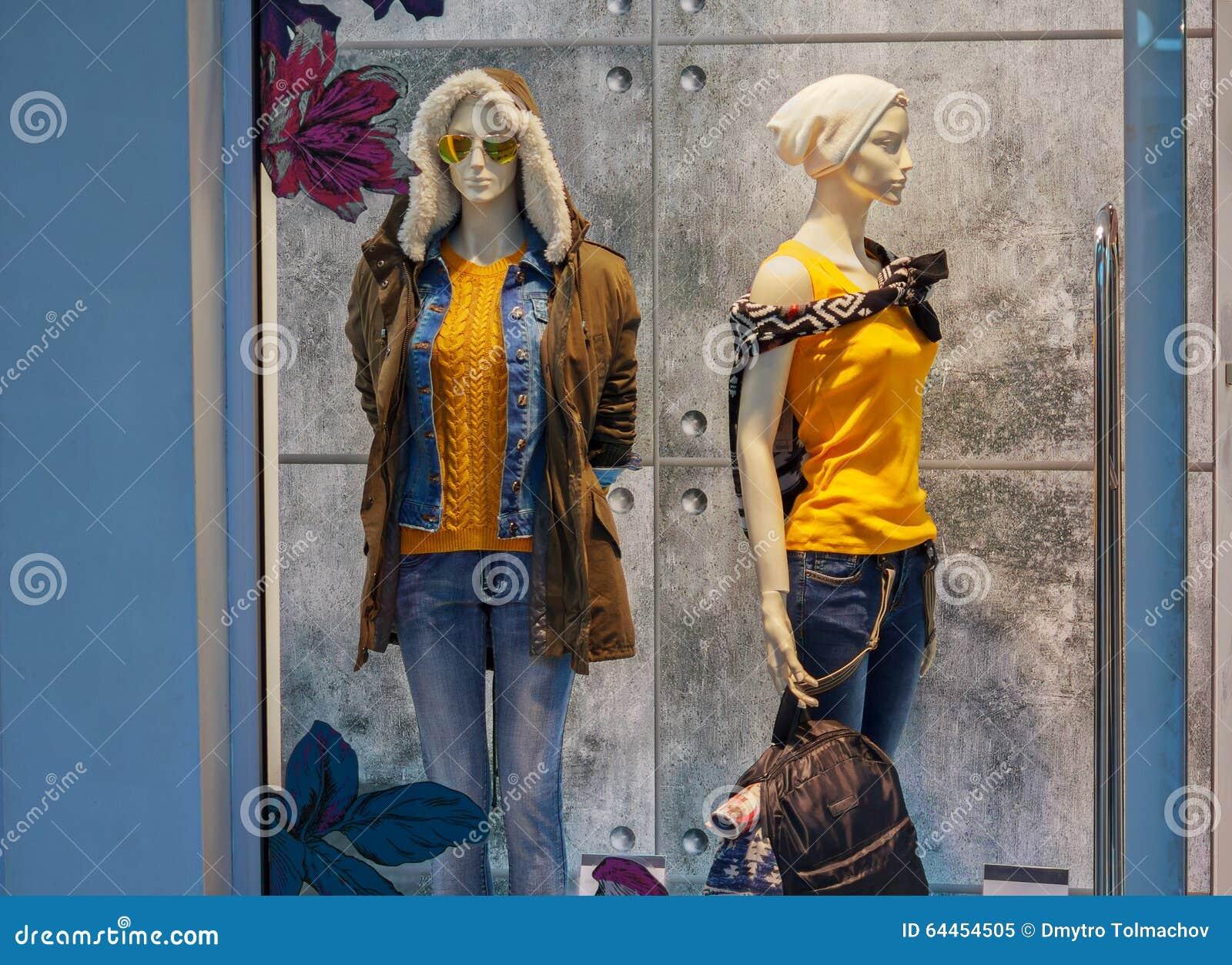 Vrouwelijke ledenpop twee in warme kleren op winkelvenster