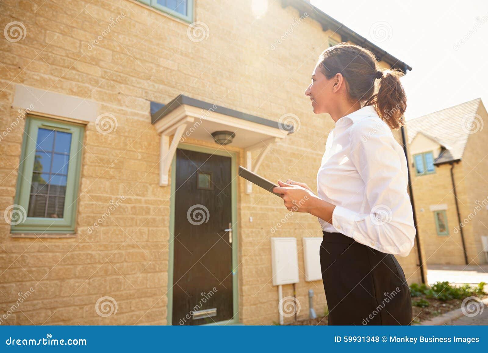 Vrouwelijke makelaar in onroerend goed die een huisbuitenkant bekijken