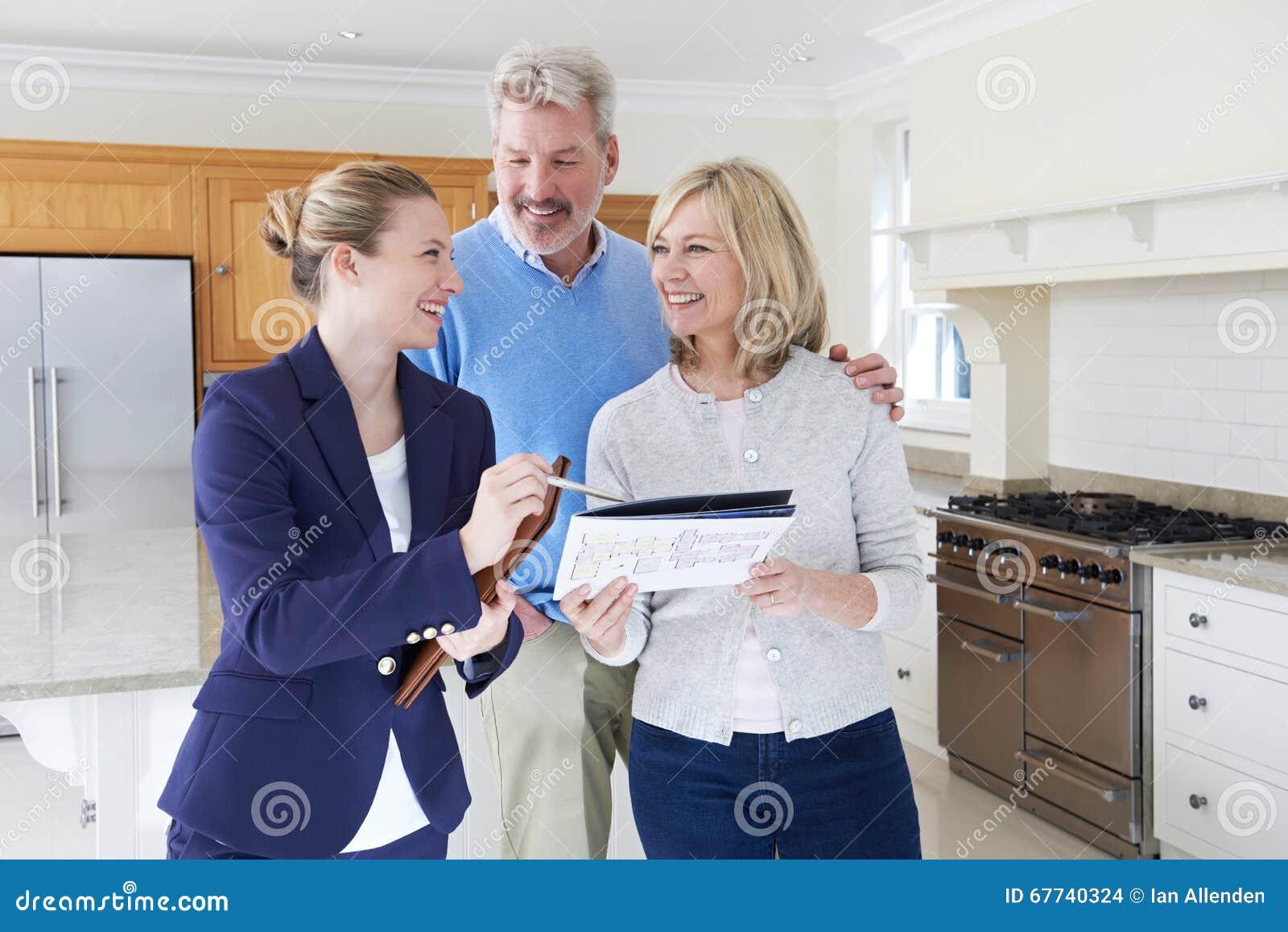 Vrouwelijke Makelaar in onroerend goed die Rijp Paar tonen rond Huis voor Verkoop