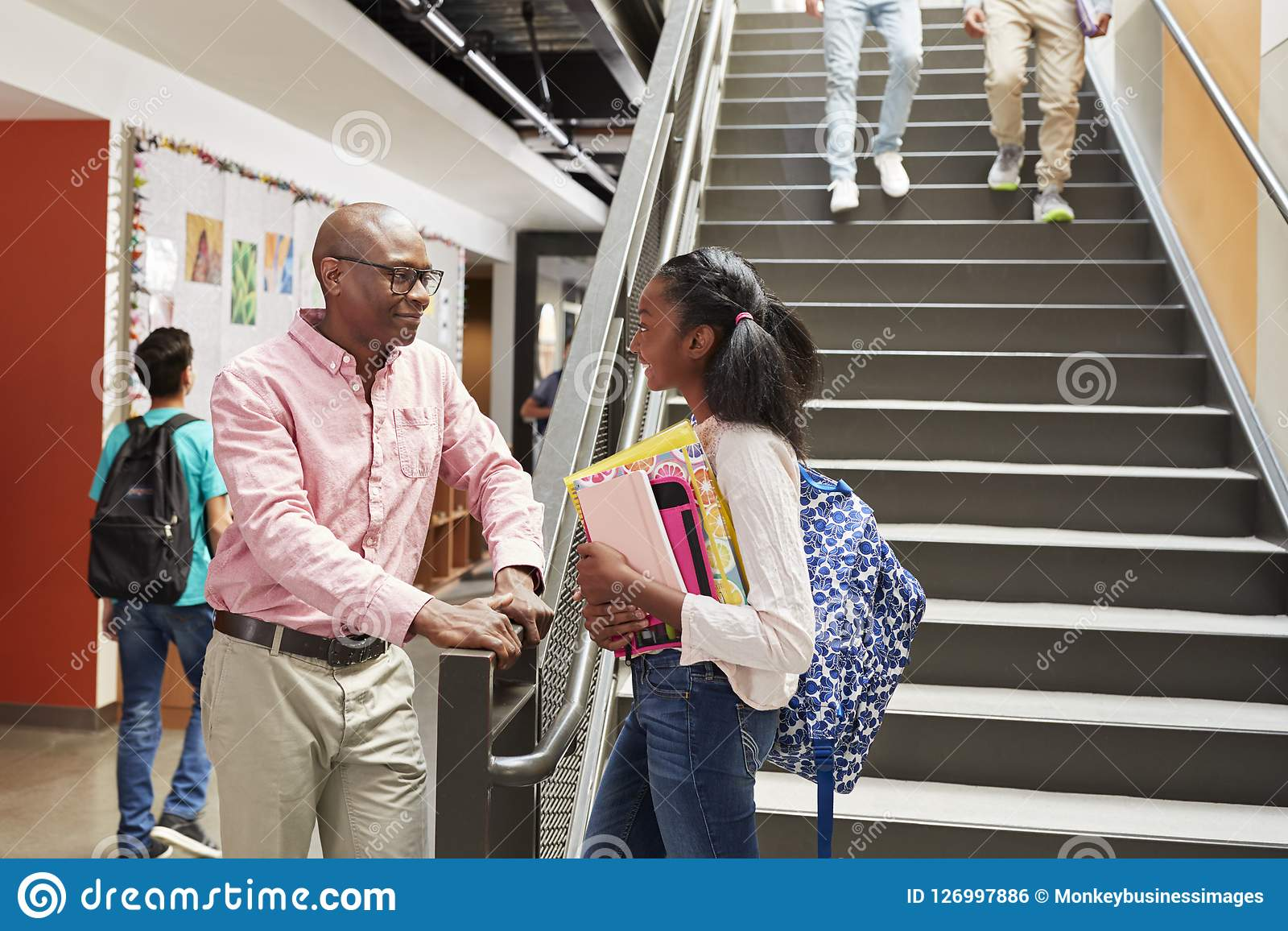 Vrouwelijke Middelbare schoolstudent Talking With Teacher in Bezige Gang