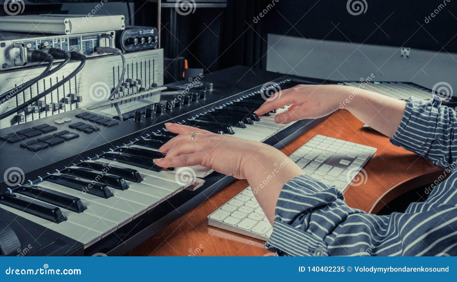 Vrouwelijke musicus die het toetsenbordsynthesizer van Midi in opnamestudio spelen, nadruk op handen De wapensspelen van de vrouw