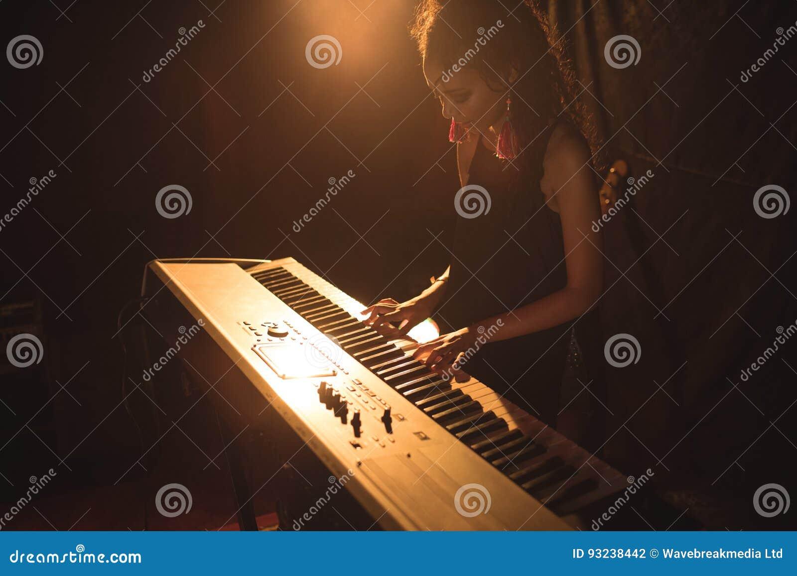 Vrouwelijke musicus het spelen piano in verlichte nachtclub