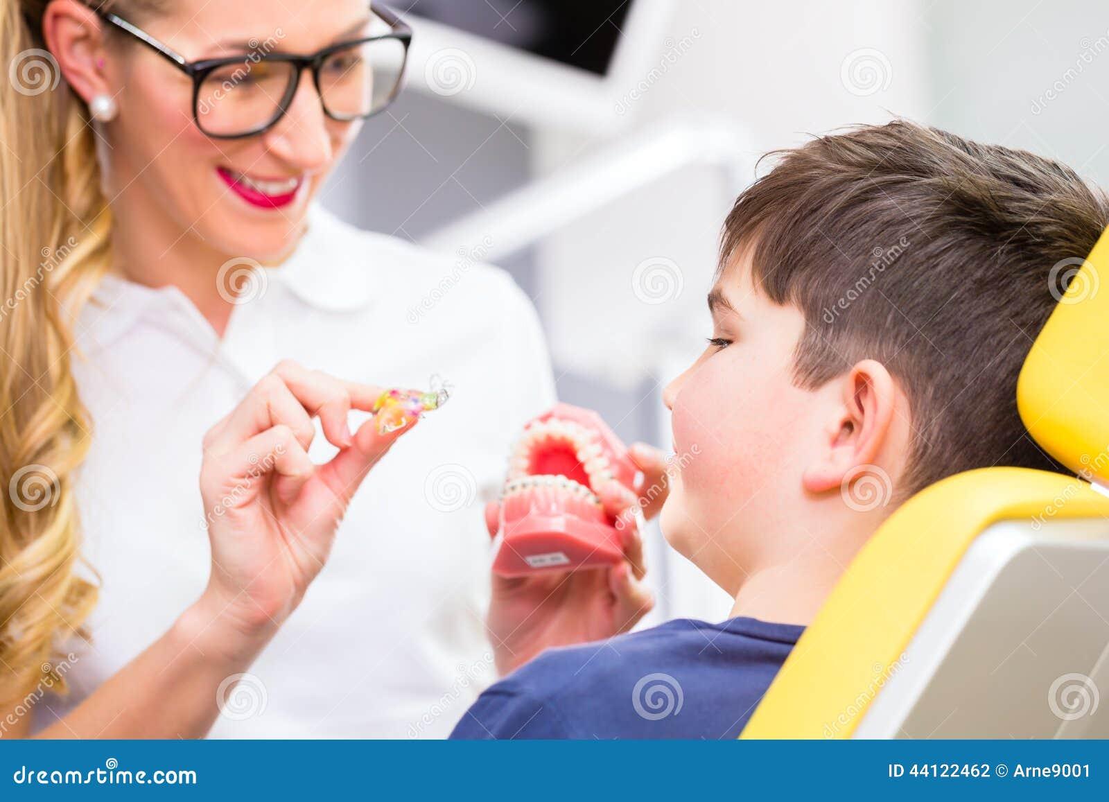 Vrouwelijke Orthodontist die jongen verklaren