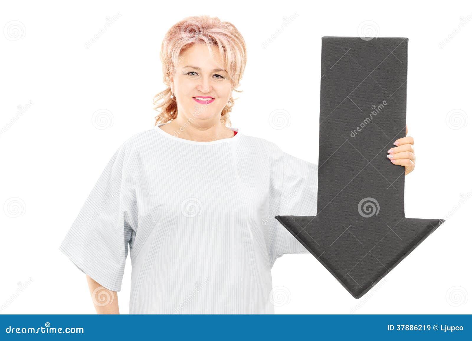 Vrouwelijke patiënt die in het ziekenhuistoga het grote zwarte pijl richten houdt