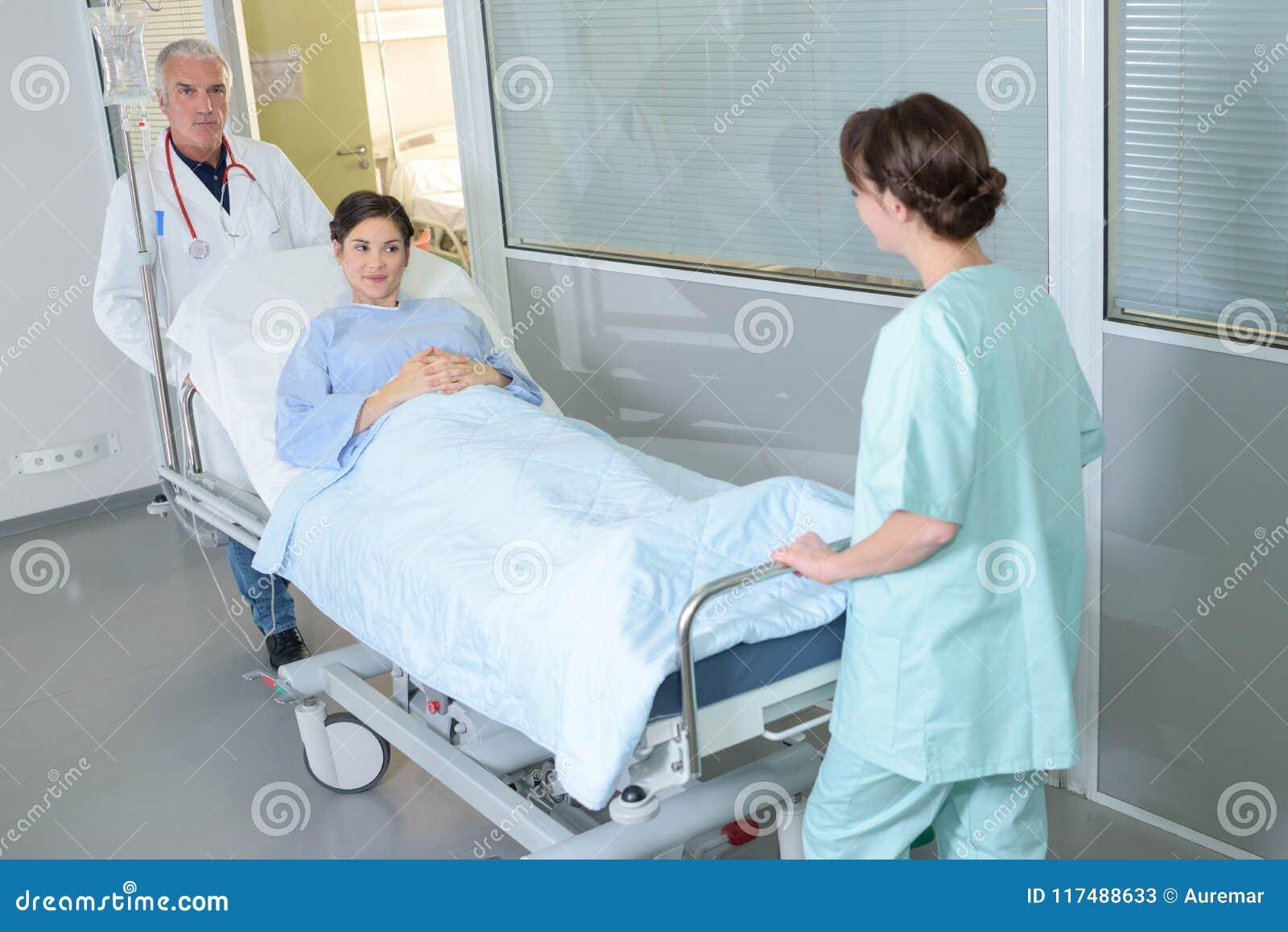 Vrouwelijke patiënt die op brancard of gurney in het ziekenhuis worden geduwd