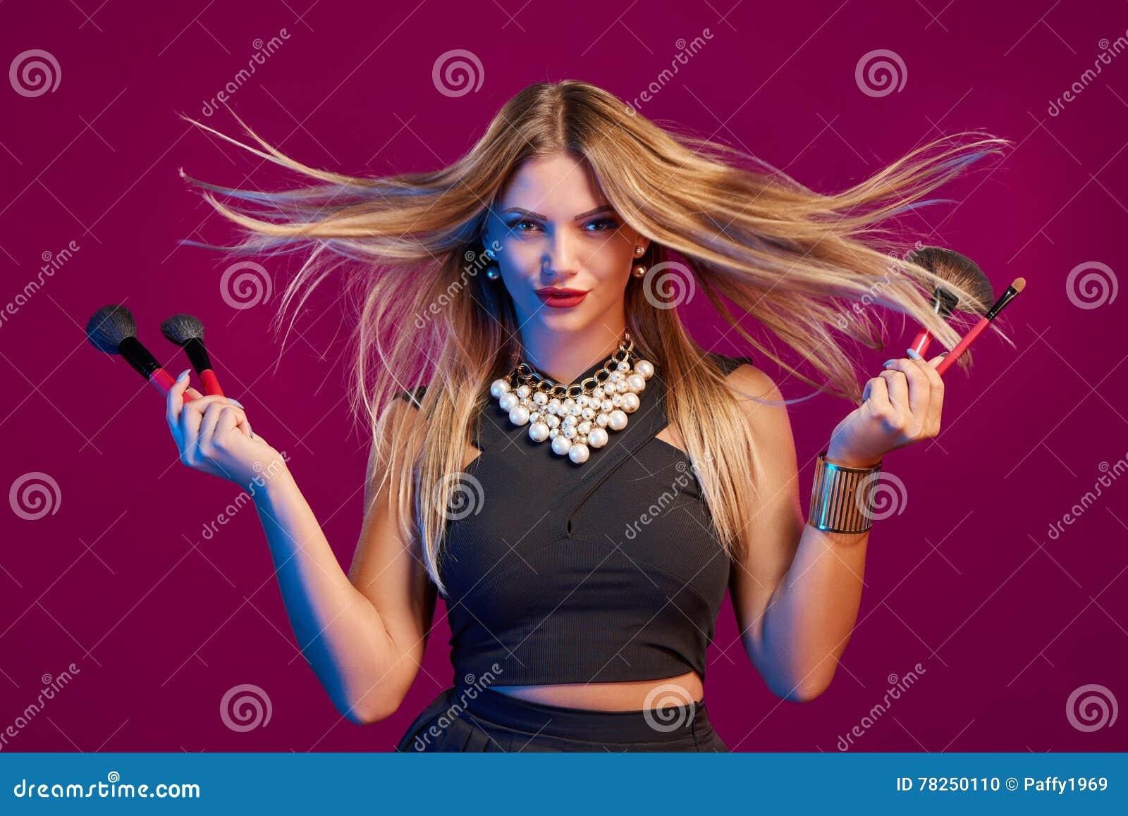 Vrouwelijke stilist met de make-upborstels van de haar vliegende holding