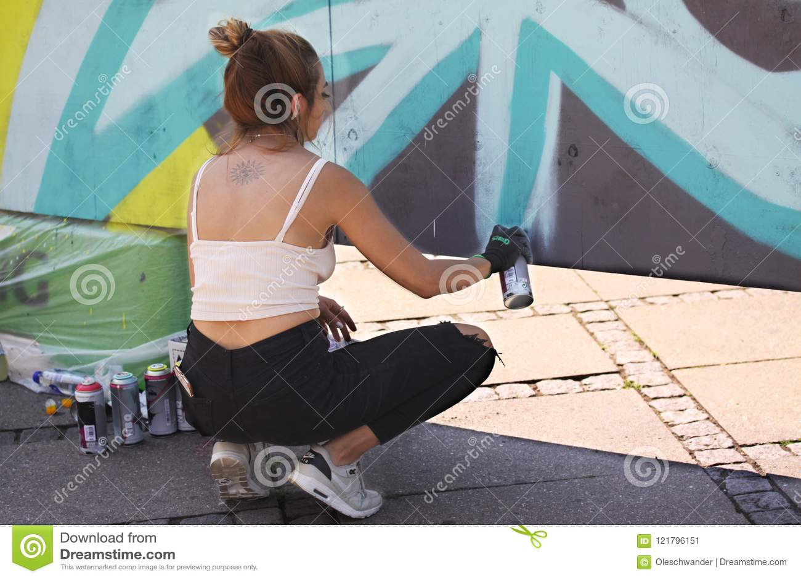 Vrouwelijke straatkunstenaar die kleurrijke graffiti op muur schilderen - Modern kunstconcept met het stedelijke meisje schildere