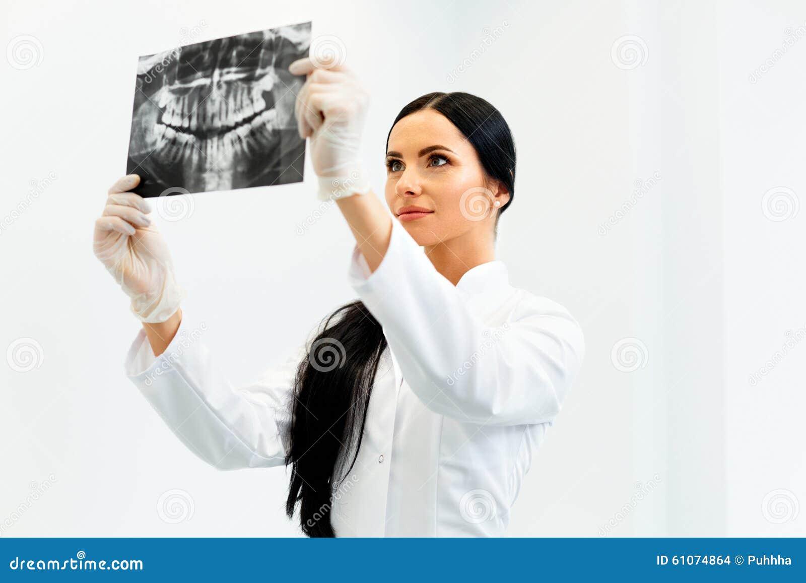 Vrouwelijke Tandarts Looking bij Tandröntgenstraal in Kliniek