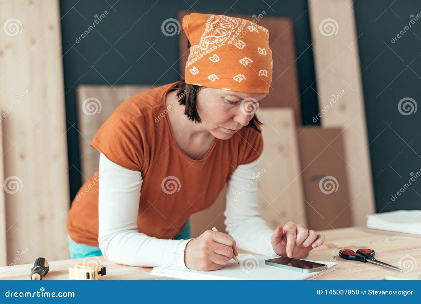 Vrouwelijke timmerman die financi?le berekening doen
