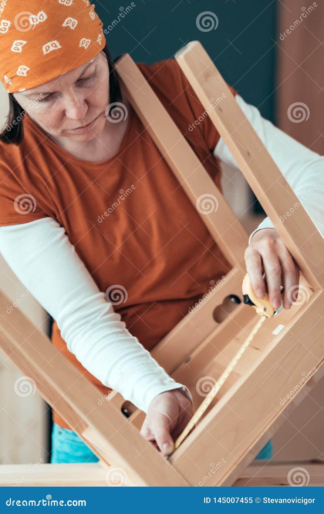 Vrouwelijke timmermansband die houten stoelzetel in workshop meten