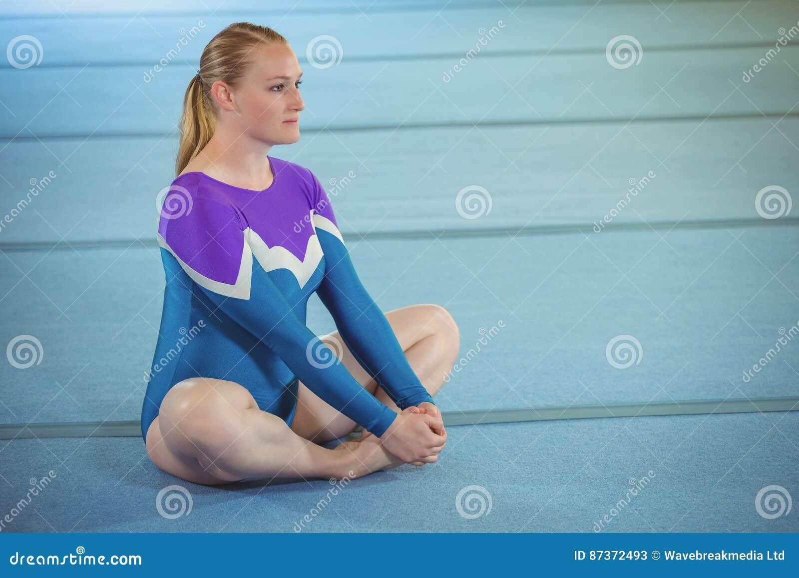 Vrouwelijke turner die uitrekkende oefening uitvoeren