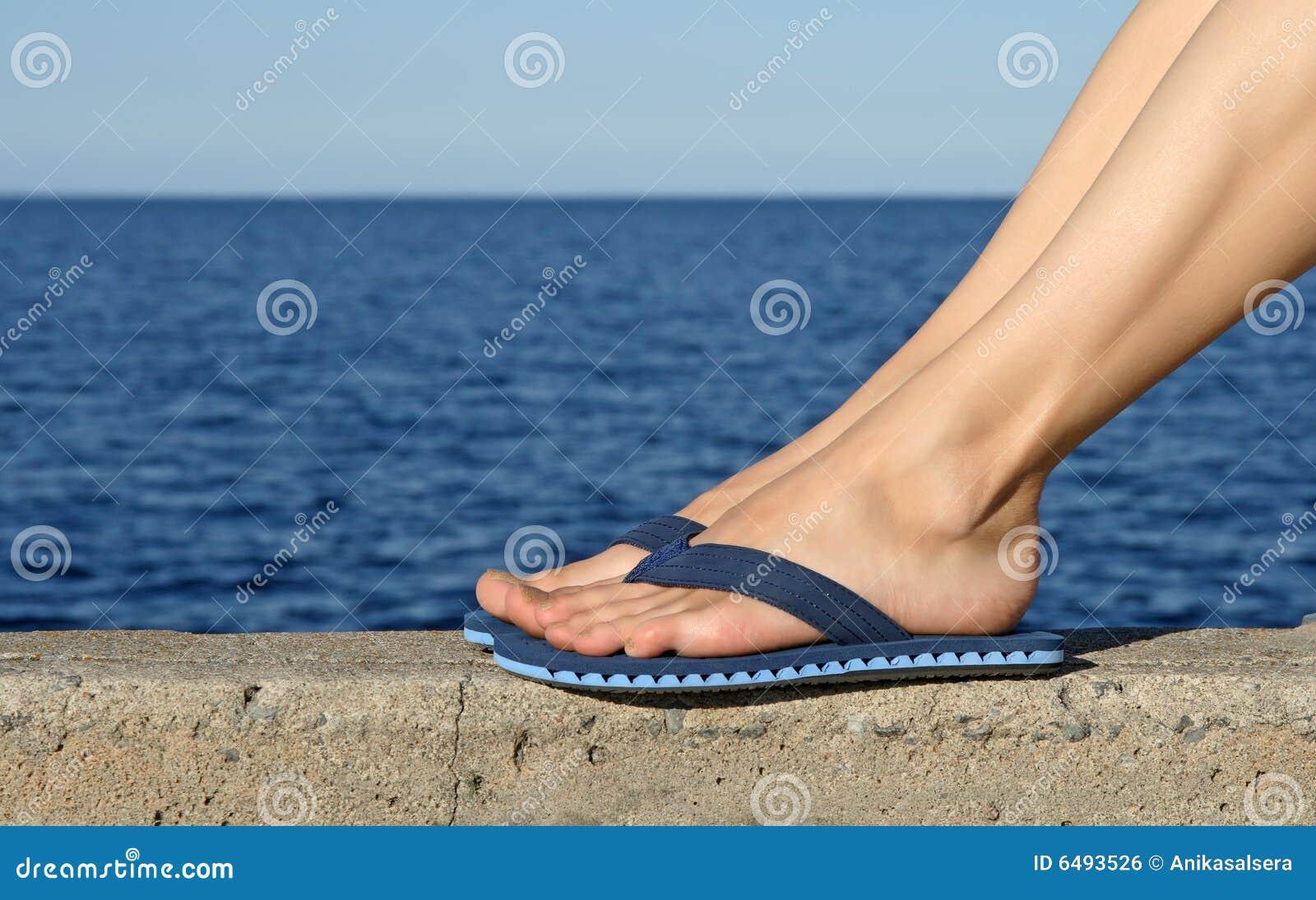 Vrouwelijke voeten die blauwe wipschakelaars dragen