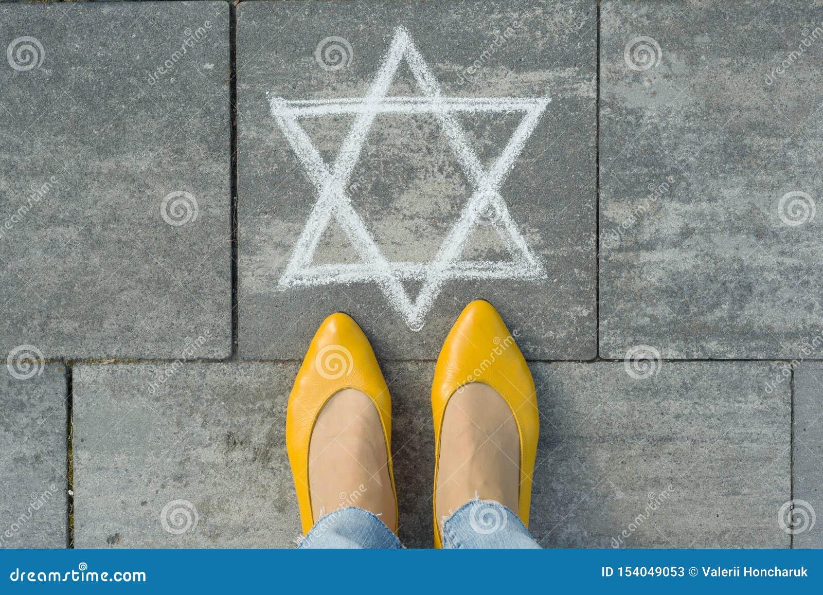 Vrouwelijke voeten met abstract beeld van zes gerichte die ster, op grijze stoep wordt geschreven