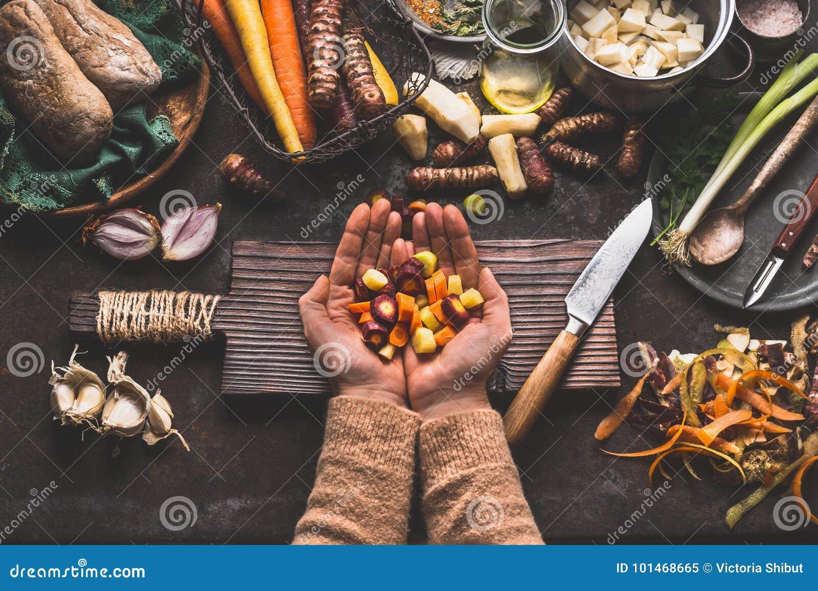 Vrouwelijke vrouwenhanden die gedobbelde kleurrijke groenten op rustieke keukenlijst houden met vegetarische kokende ingrediënten