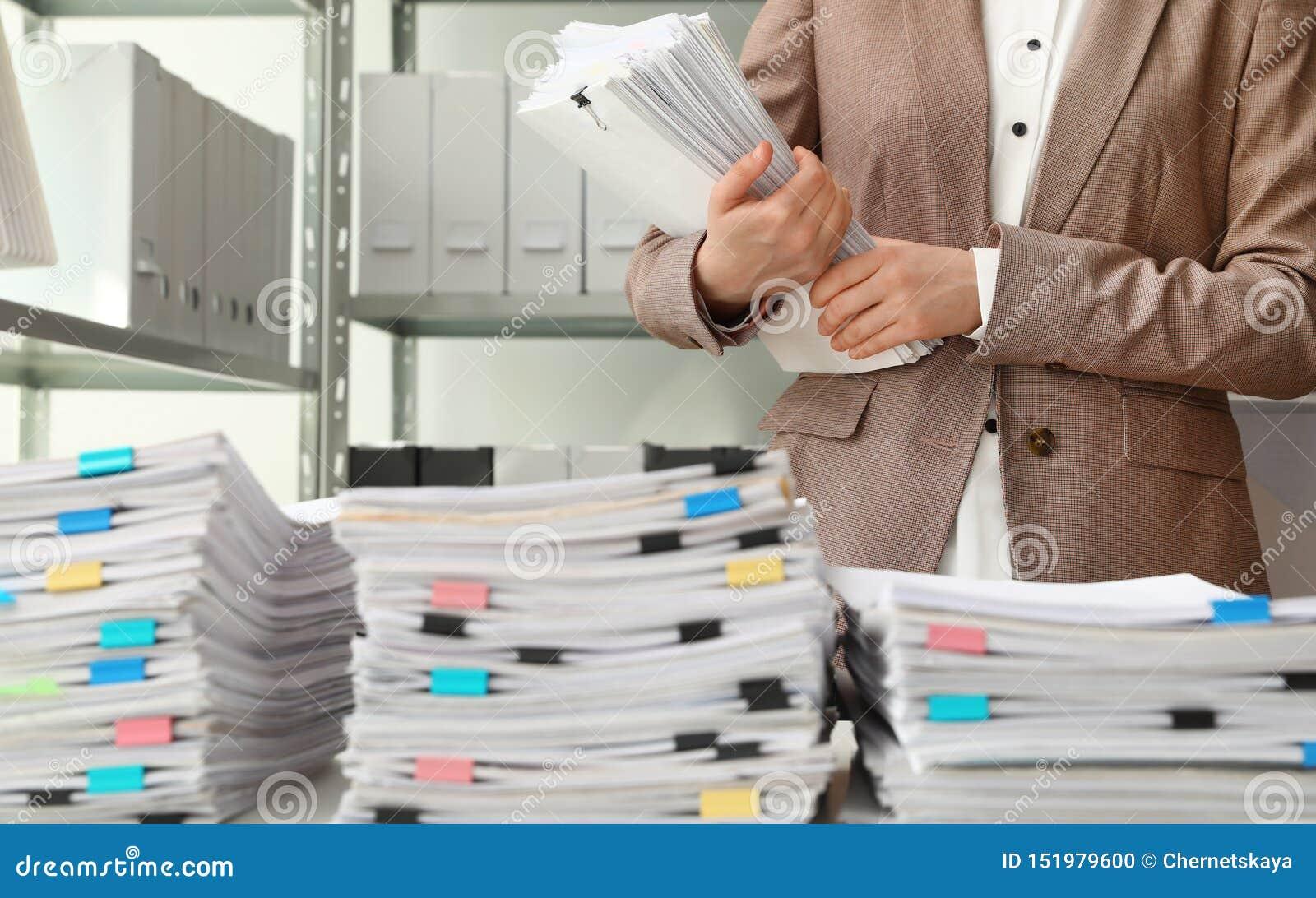 Vrouwelijke werknemer met documenten in archief