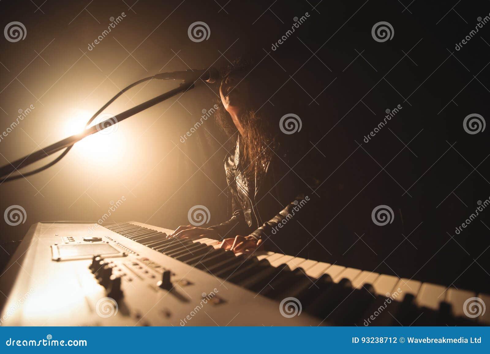 Vrouwelijke zanger het spelen piano terwijl het presteren in muziekoverleg