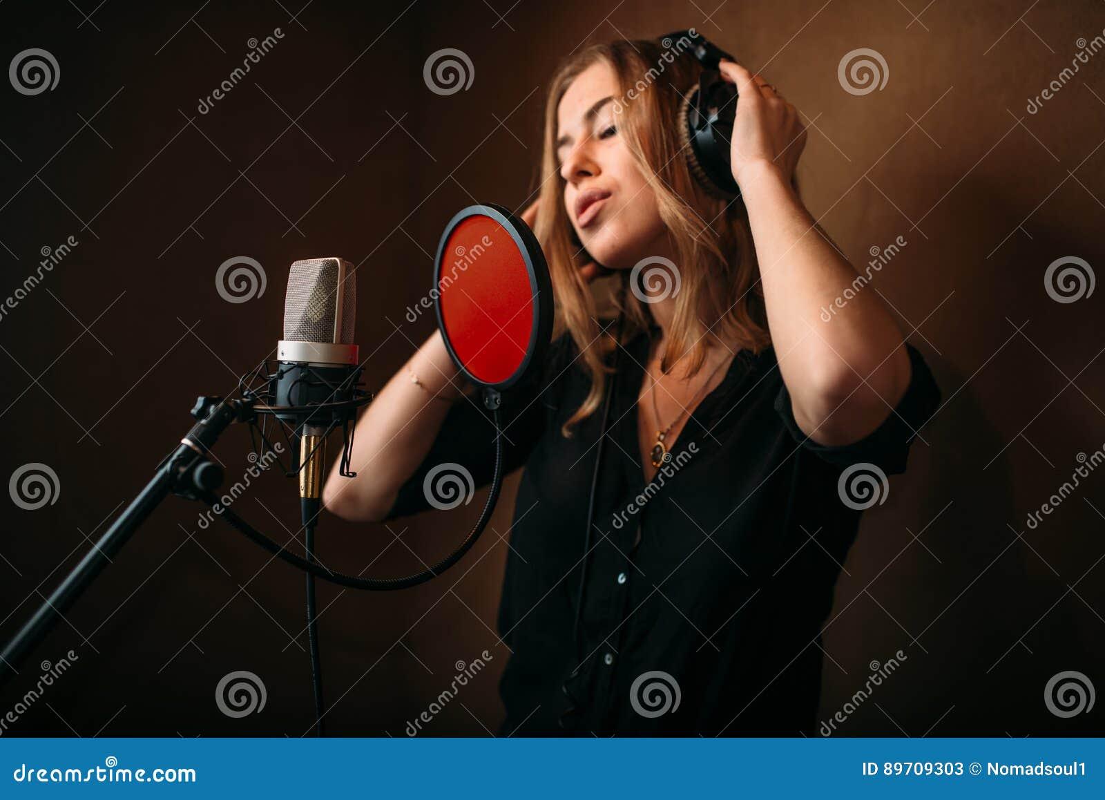 Vrouwelijke zanger in hoofdtelefoons tegen microfoon