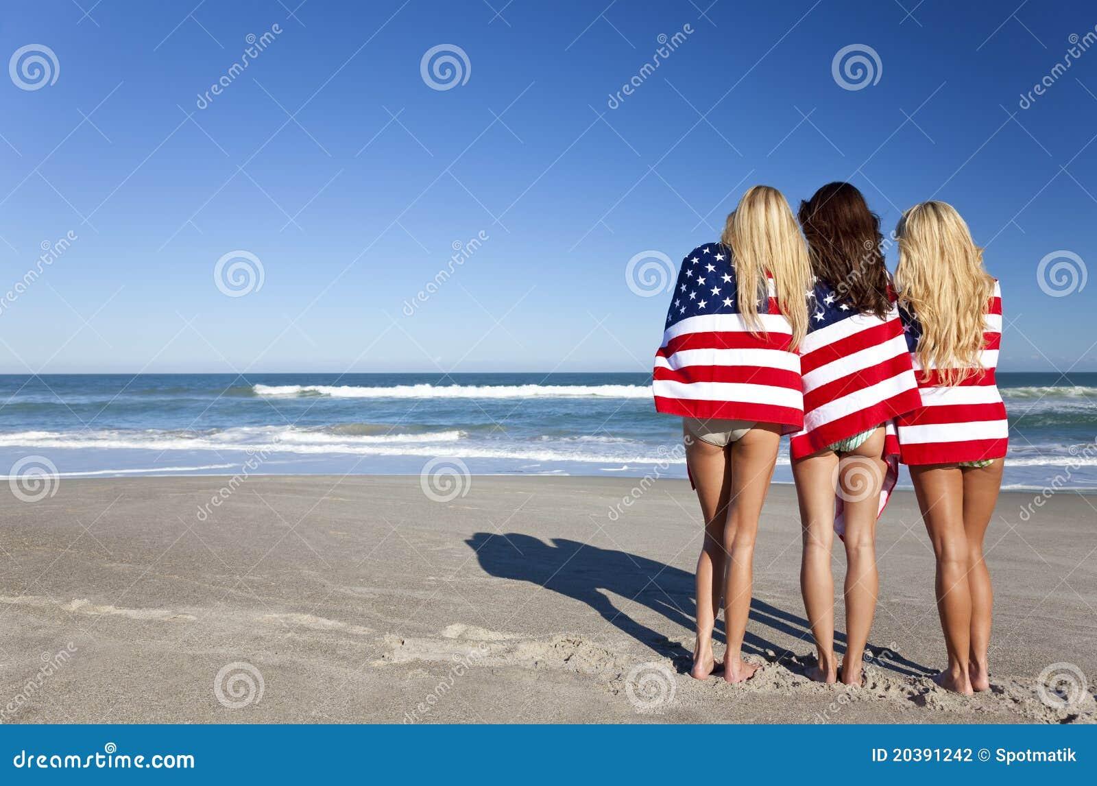Vrouwen die in Amerikaanse Vlaggen op een Strand worden verpakt