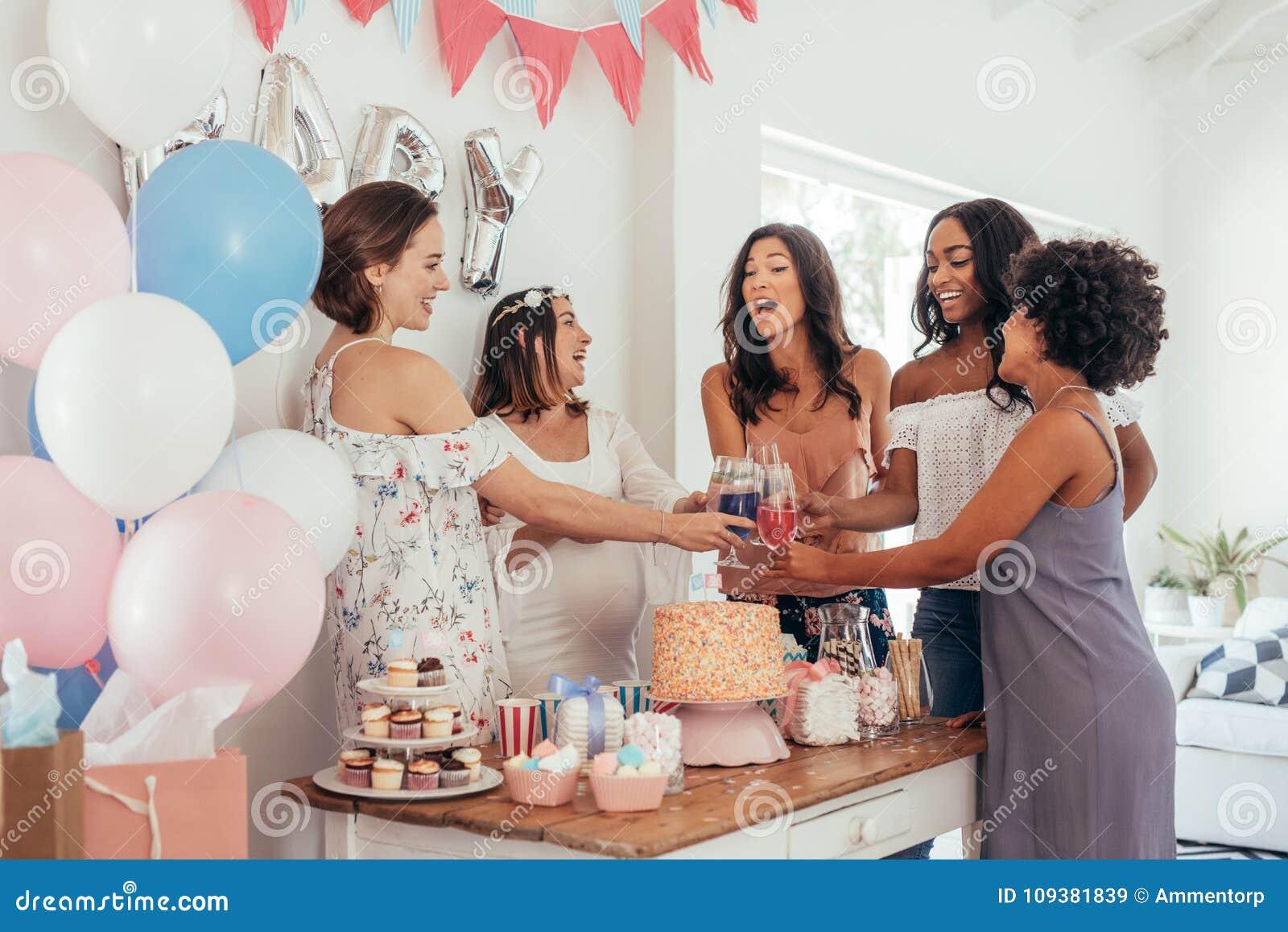 Vrouwen die met sappen bij de partij van de babydouche roosteren