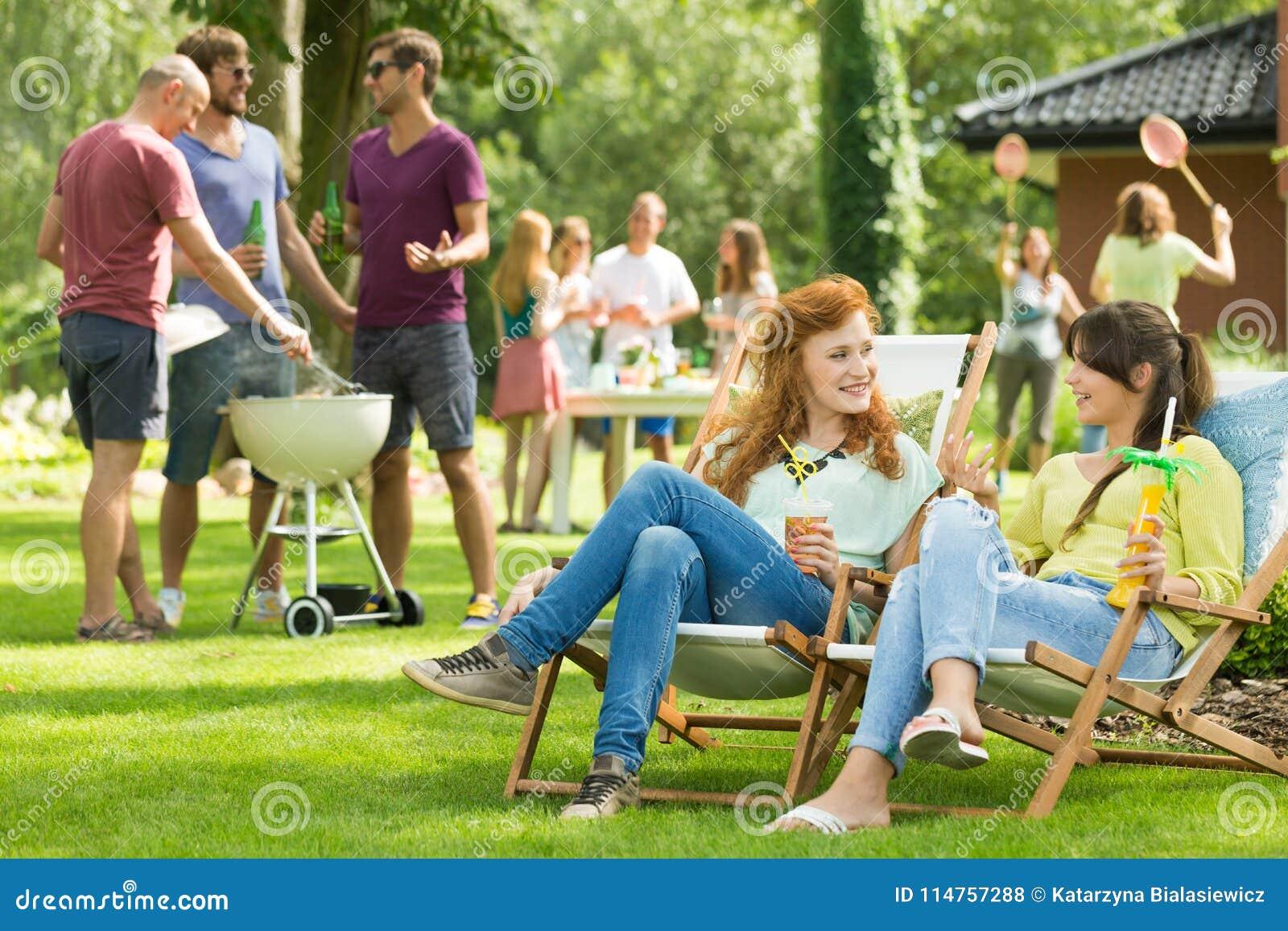 Vrouwen die op een tuinpartij babbelen
