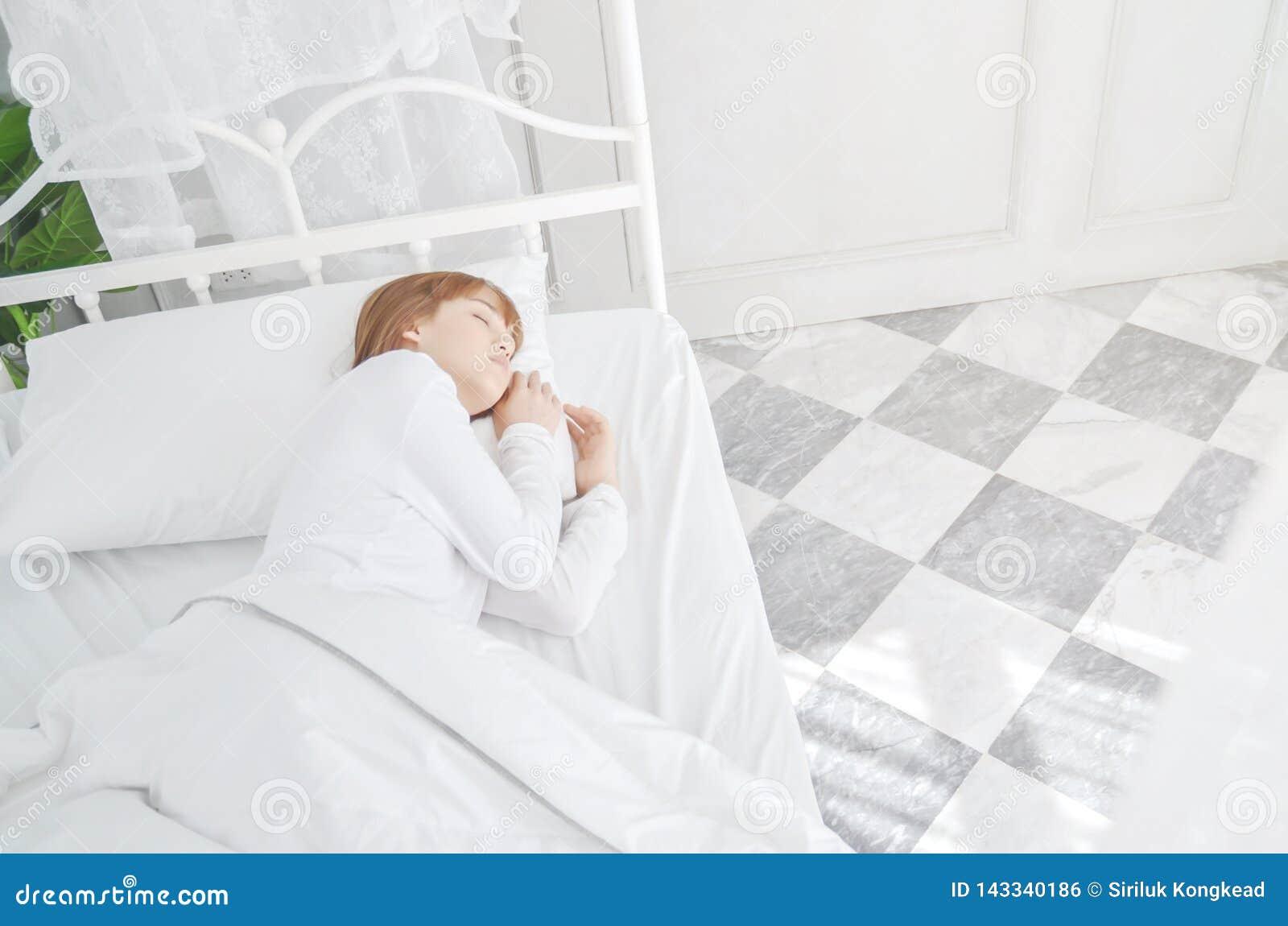 Vrouwen die witte pyjama srust op de matras dragen