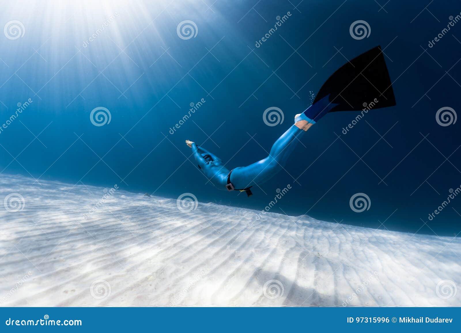 Vrouwen freediver glijdende bewegingen over zandige bodem