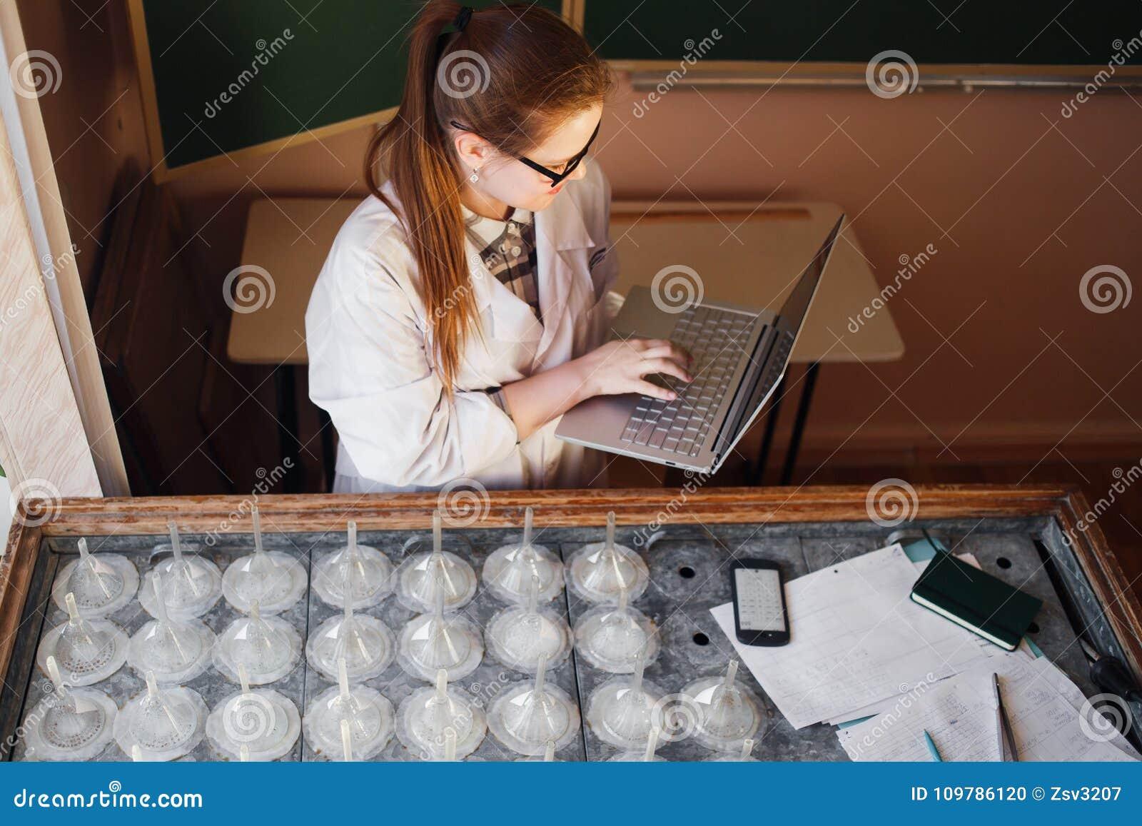 Vrouwen gediplomeerde student die aan laptop computer in biotechnologielaboratorium werken