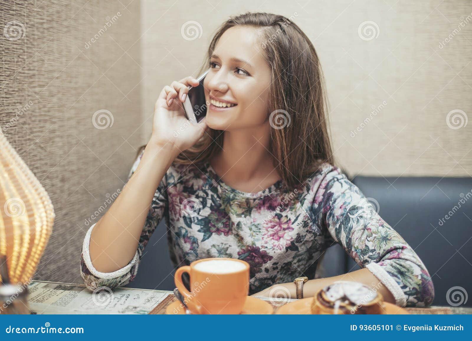 Vrouwen mooi model in de koffiewinkel met gebakjes en telefoon