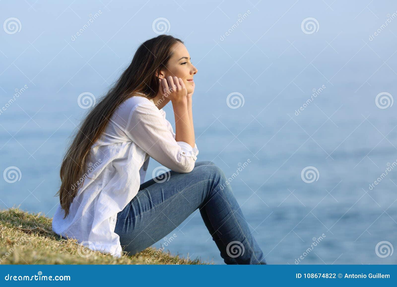 Vrouwen ontspannende zitting op het gras die op het overzees letten