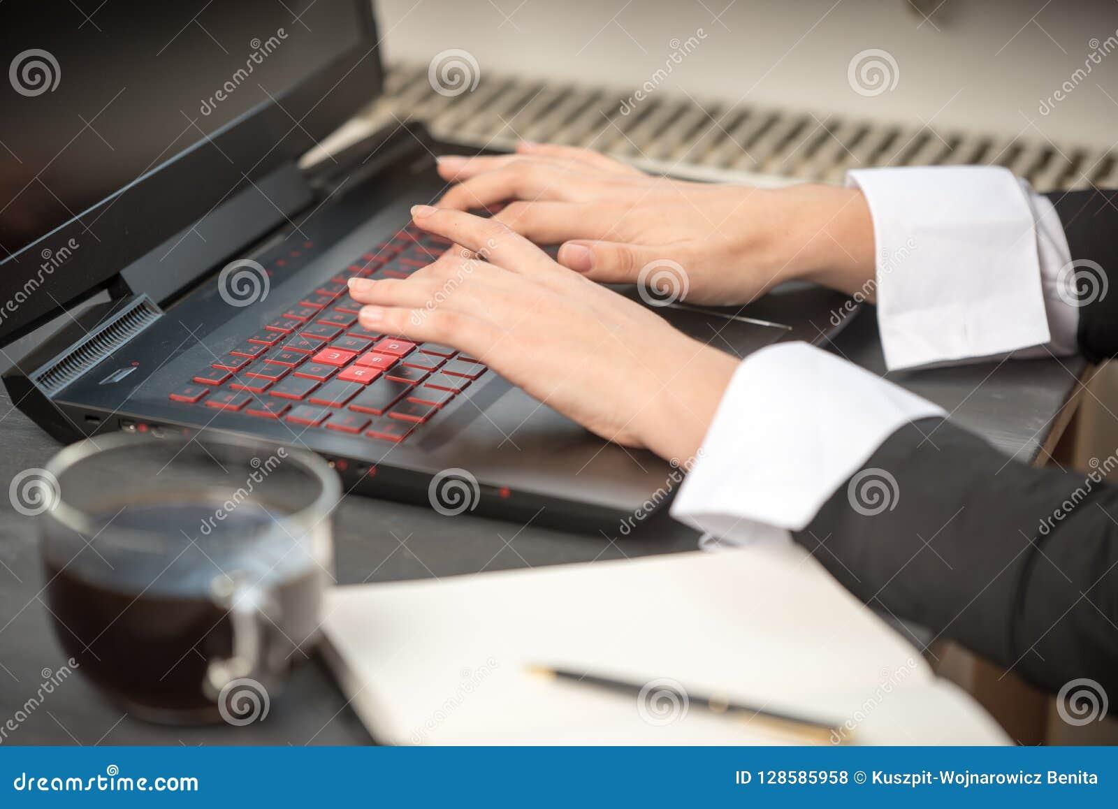 Vrouwen` s hand op een zwart-en-rood laptop toetsenbord