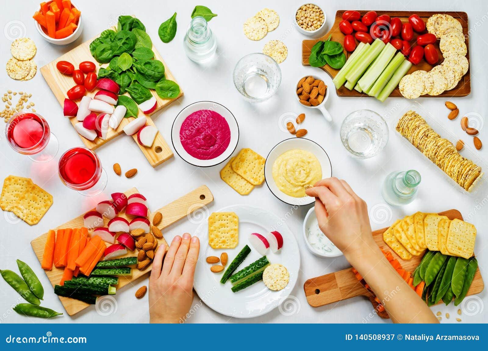 Vrouwen` s handen en variatie van gezonde veganistsnacks Groenten, crackers, onderdompeling en hummus