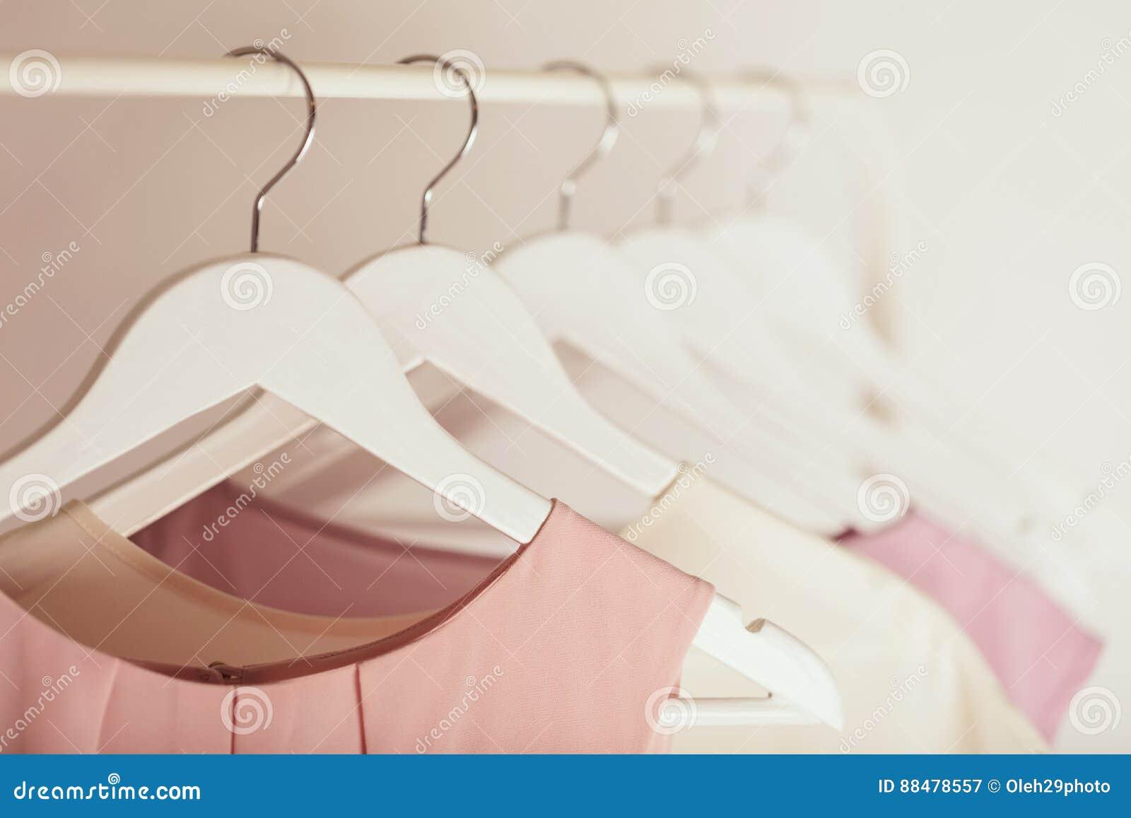 Vrouwen` s kleding in roze tonen op een witte hanger