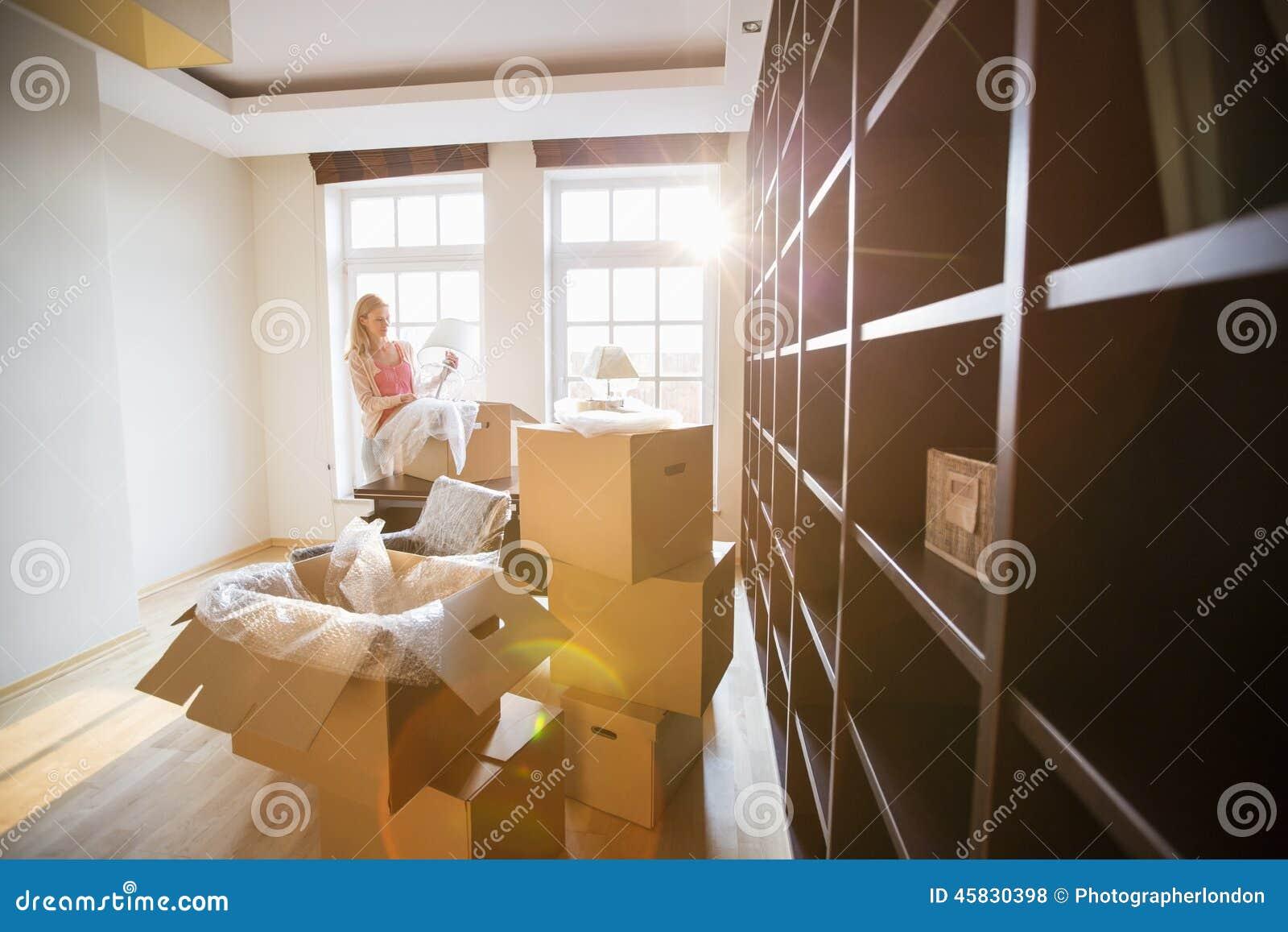 Vrouwen uitpakkende lamp van het bewegen van doos bij nieuw huis