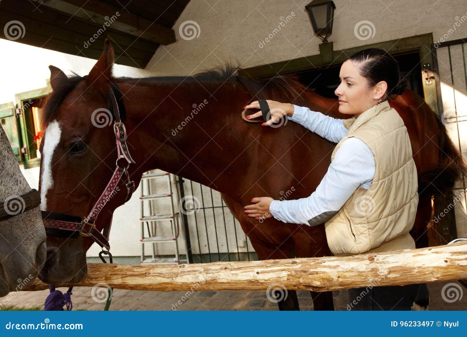 Vrouwen verzorgend paard