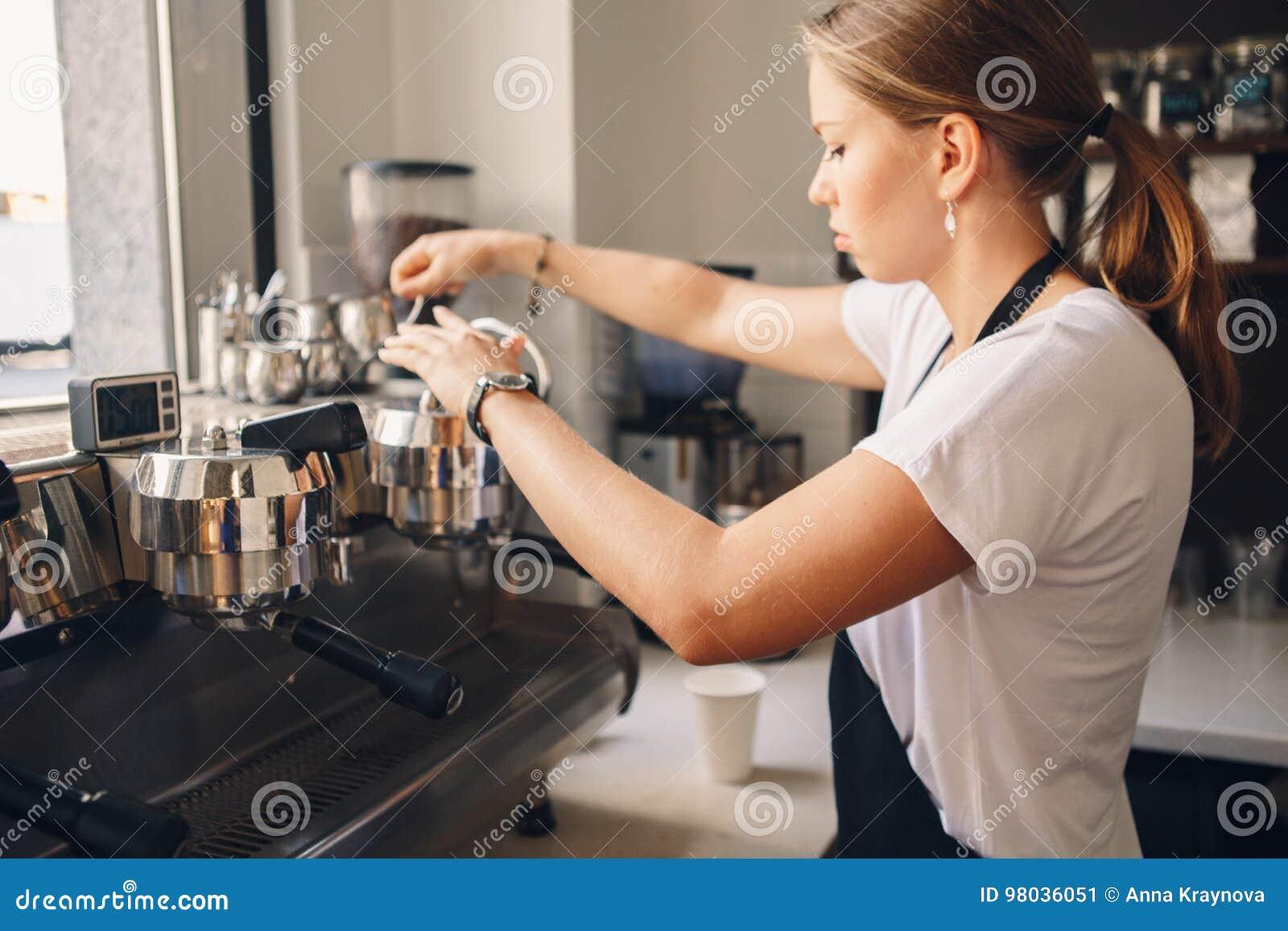 Vrouwenbarista die koffie in winkel maken