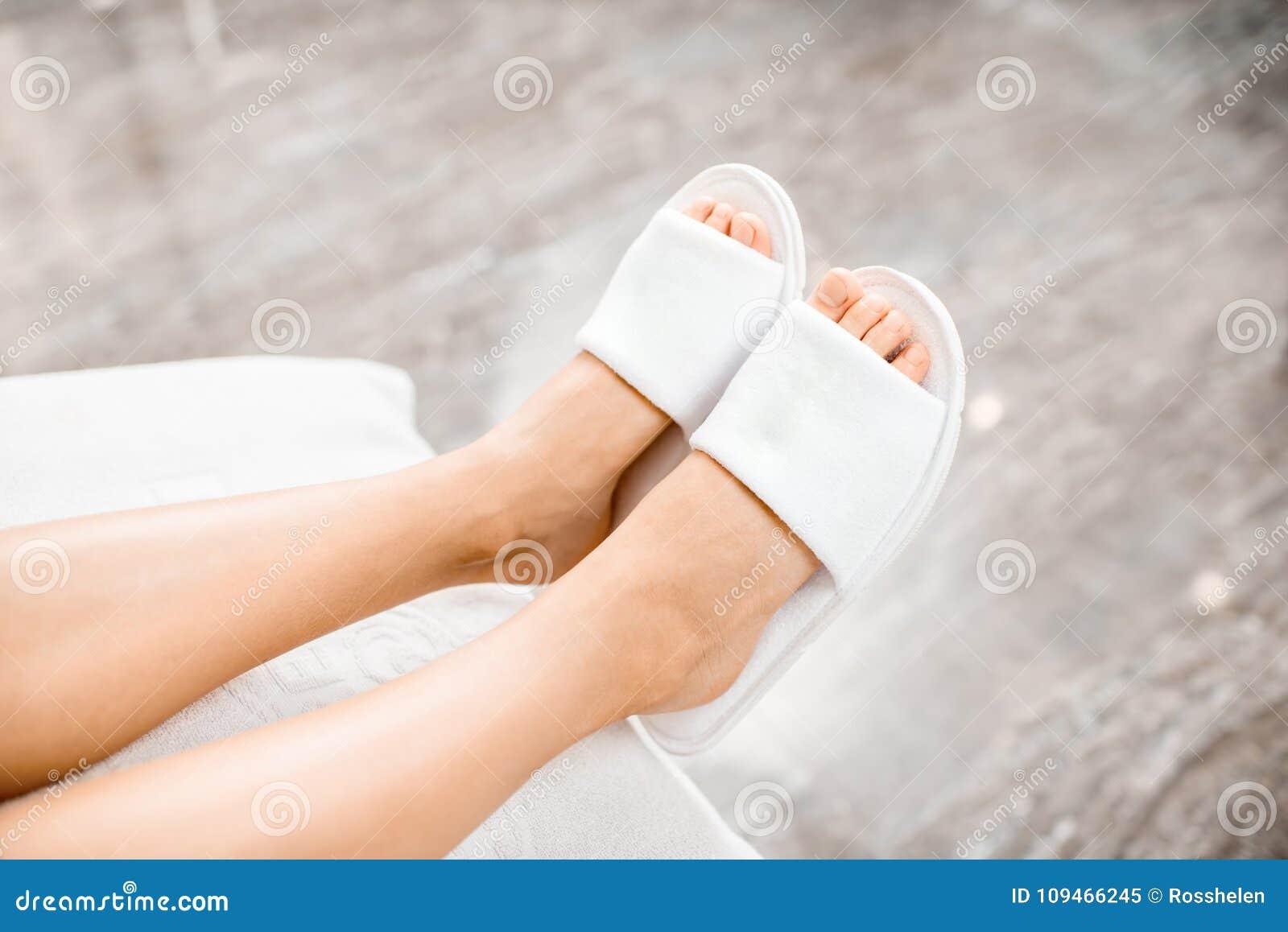 Vrouwenbenen in badpantoffels