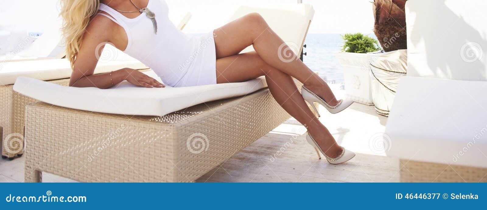 Vrouwenbenen op een zonlanterfanter