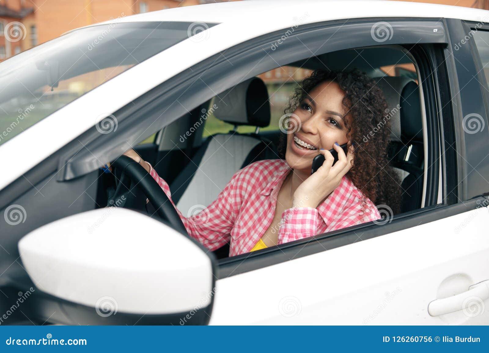 Vrouwenbestuurder die haar mobiele telefoon met behulp van terwijl het drijven van auto