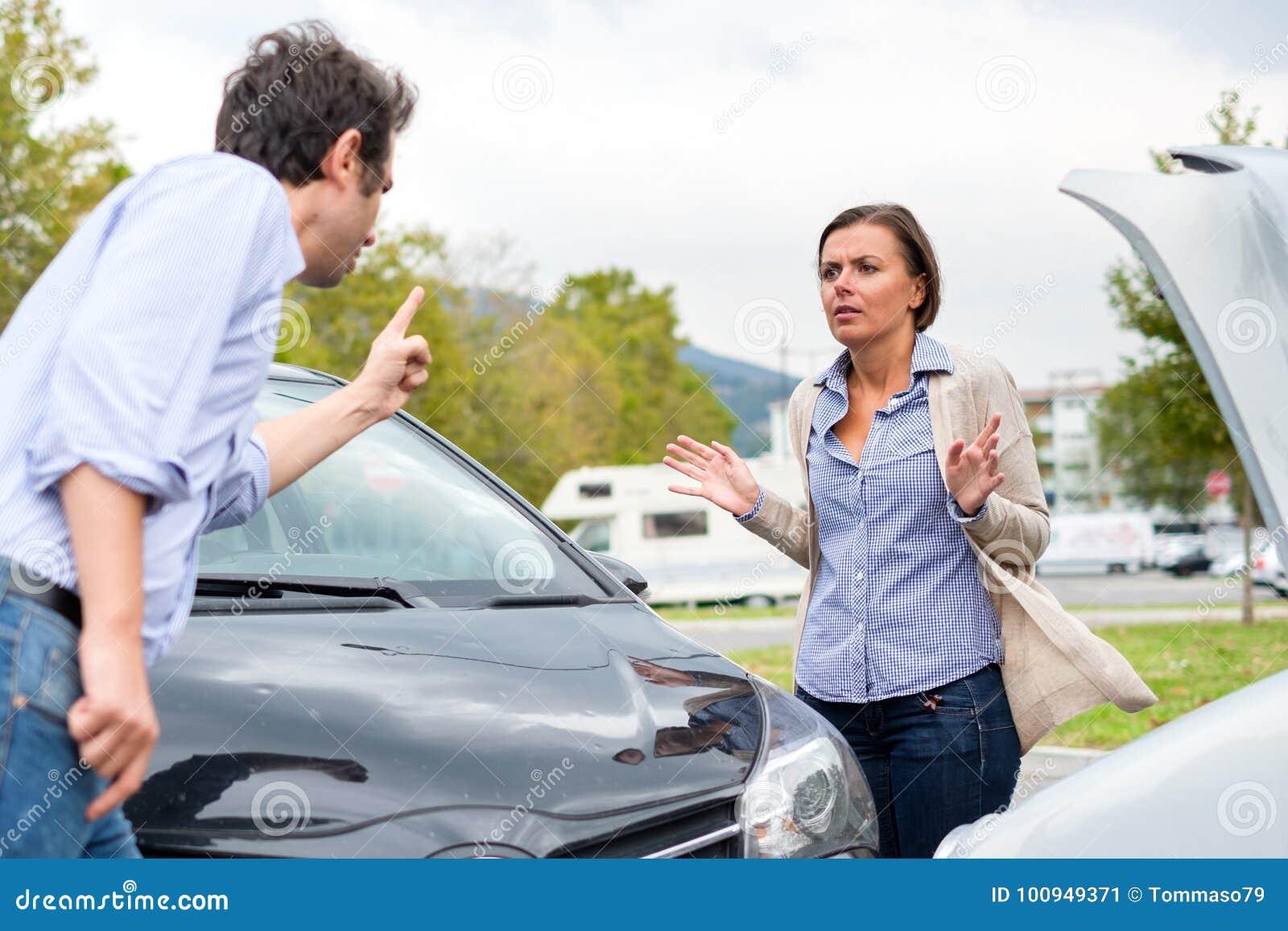 Vrouwenbestuurder en man die over de schade van de auto na a debatteren
