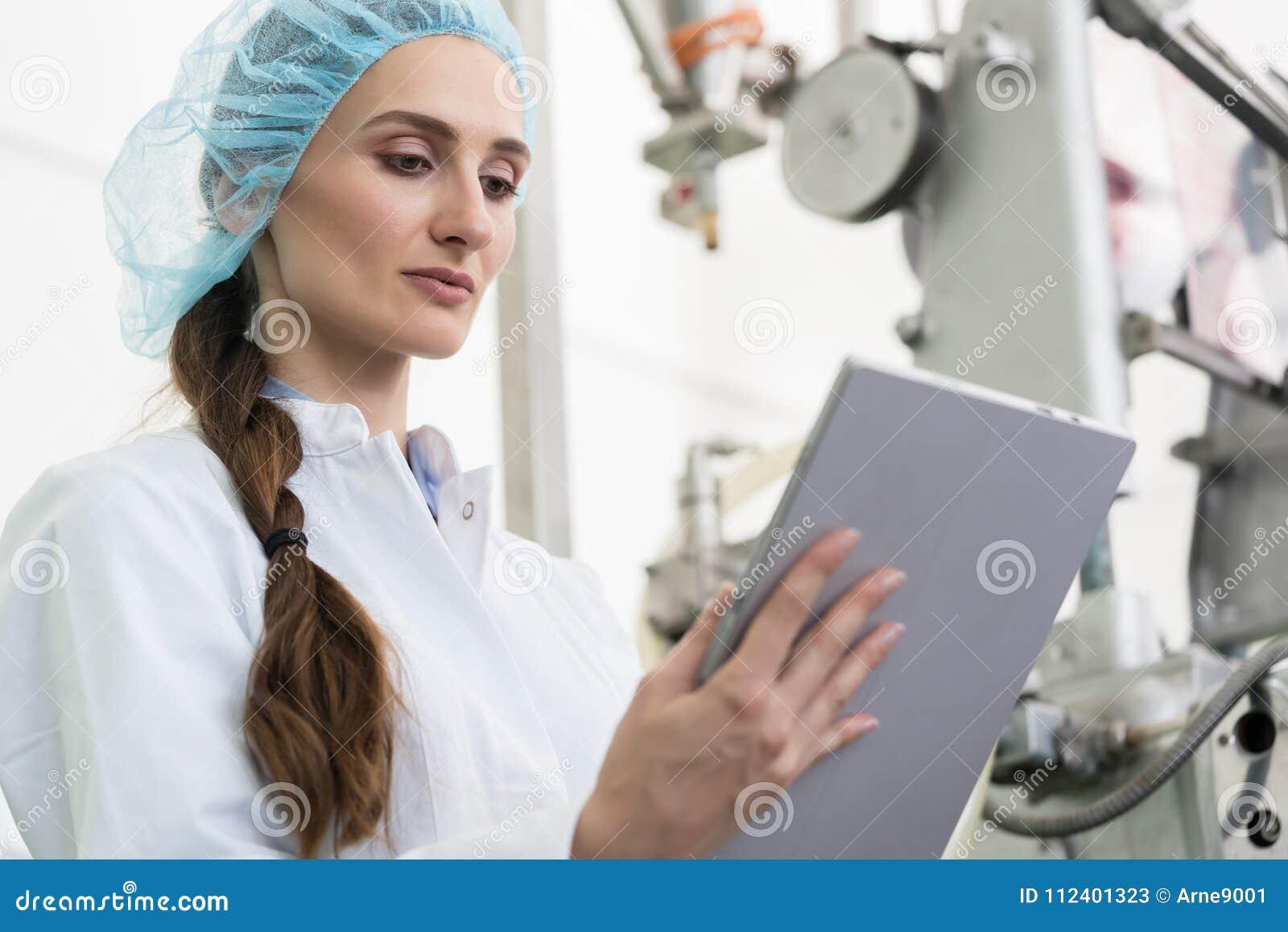 Vrouwendeskundige die informatie over tablet analyseren tijdens het werk in eigentijdse fabriek